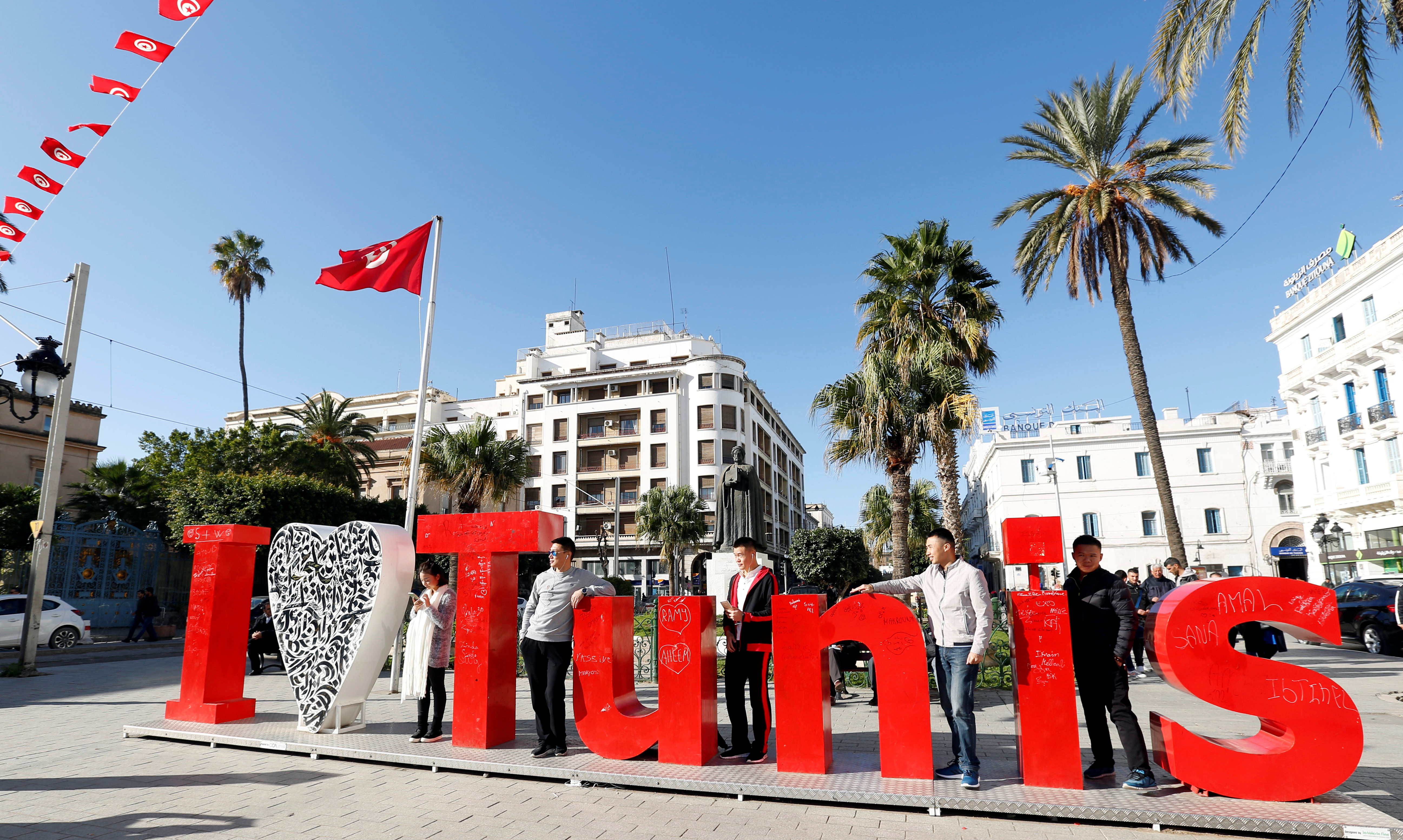 Tourists pose for a picture in downtown Tunis