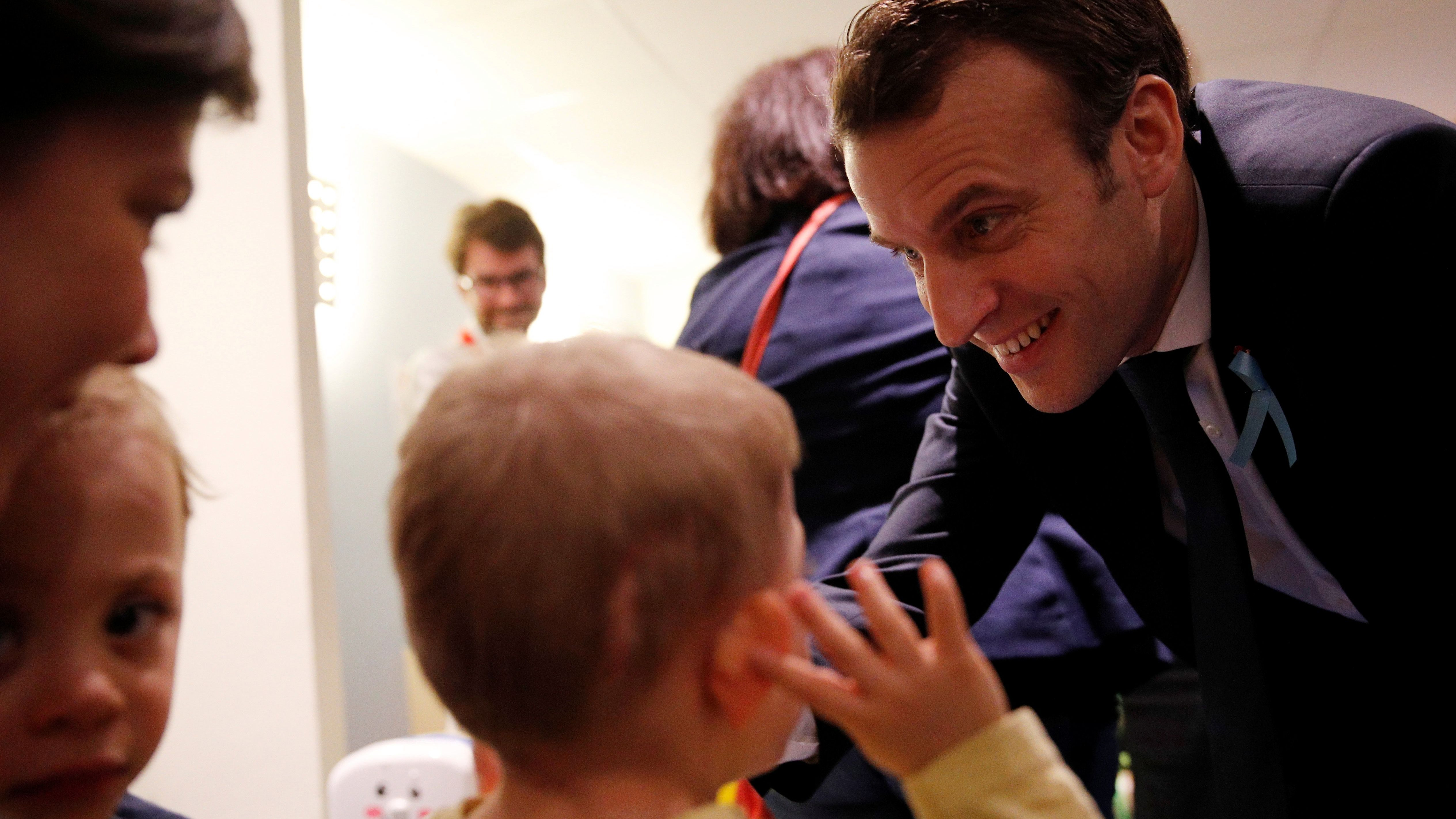 French President Emmanuel Macron smiles to a child during a visit to unveil an autism plan at the Rouen hospital, France, April 5, 2018.
