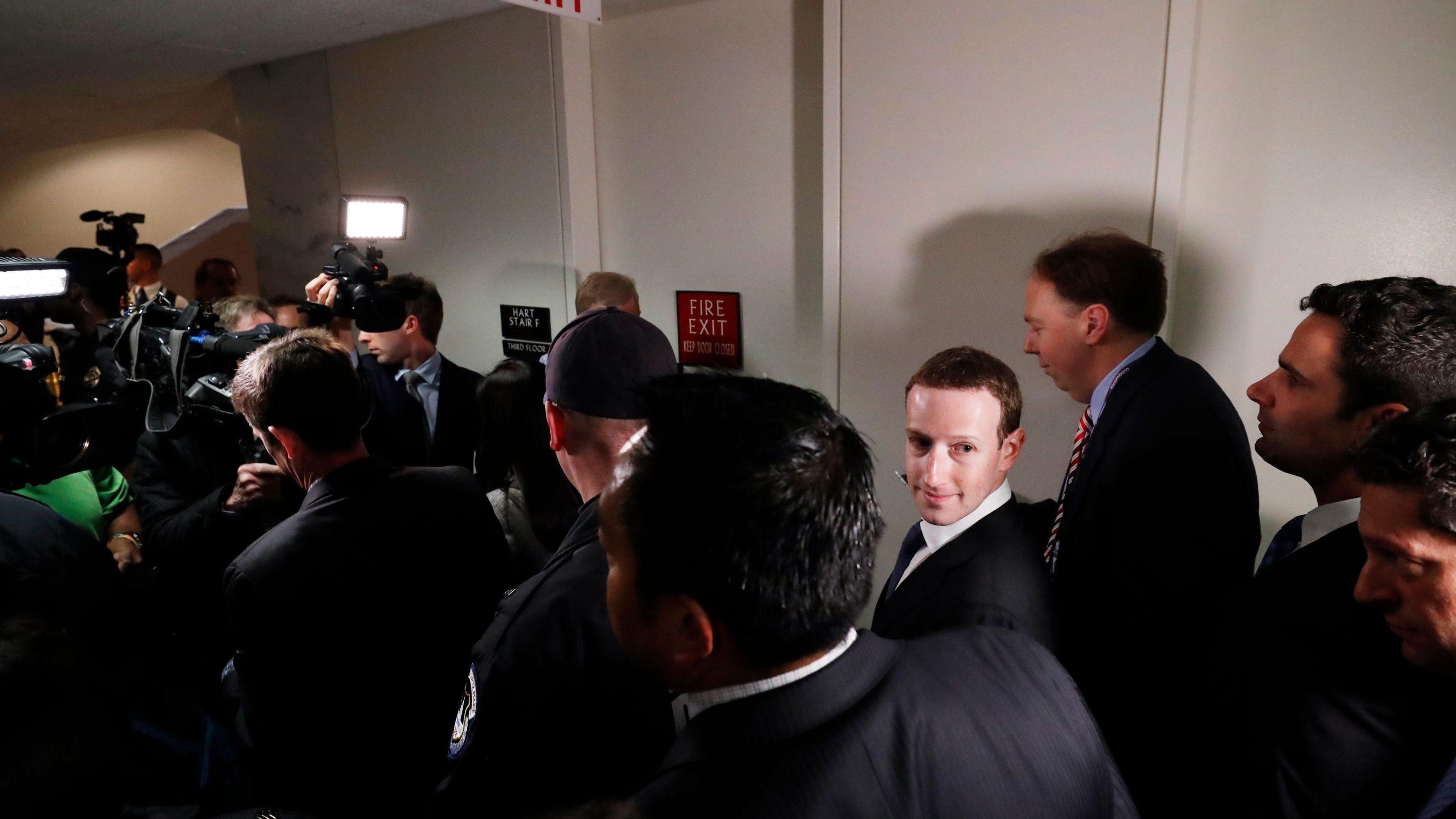 Facebook CEO Mark Zuckerberg looks back while walking to a meeting with U.S. Senator John Thune (R-SD) on Capitol Hill in Washington, U.S., April 9, 2018. REUTERS/Leah Millis - HP1EE491K0Q4C