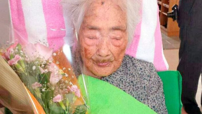 Nabi Tajima, born in 1900, holds a bouquet in Japanese southwestern island of Kikaijima, Kagoshima Prefecture, Japan, in this photo taken in 2015 and released by Kyodo. Mandatory credit Kyodo/via REUTERS     ATTENTION EDITORS -THIS IMAGE WAS PROVIDED BY A THIRD PARTY.  MANDATORY CREDIT. JAPAN OUT.  THIS IMAGE WAS PROCESSED BY REUTERS TO ENHANCE QUALITY, AN UNPROCESSED VERSION HAS BEEN PROVIDED SEPARATELY. - RC146685FB60