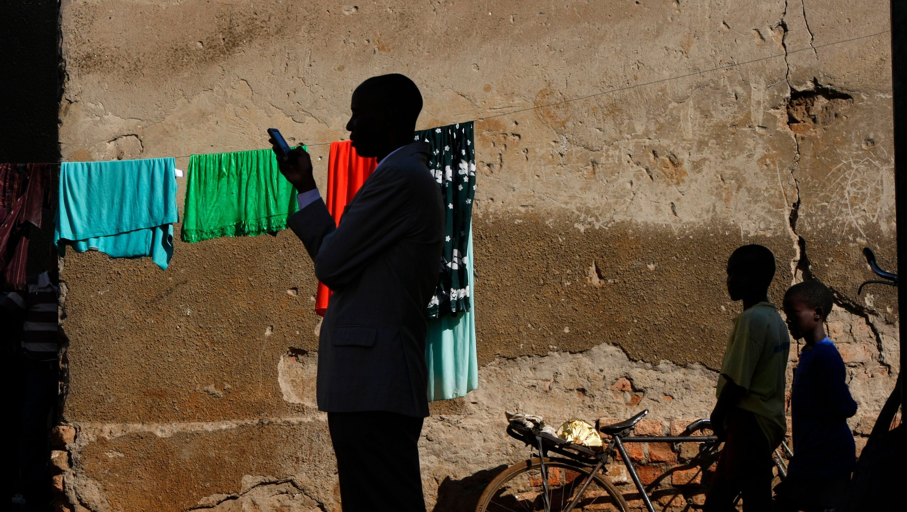 A town official accompanying visiting journalists sends a text message on his phone in the slum of Kachuf in the Masaka district of southern Uganda March 24, 2009.  The word 'Kachuf' in Luganda means 'dirt'.