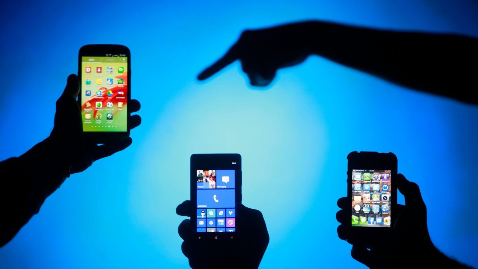 Men are silhouetted against a video screen as they pose with Samsung Galaxy S3, Nokia Lumia 820 and iPhone 4 smartphones (L-R) in this photo illustration taken in the central Bosnian town of Zenica, May 17, 2013. REUTERS/Dado Ruvic (BOSNIA AND HERZEGOVINA - Tags: BUSINESS TELECOMS) - BM2E95H0URU01