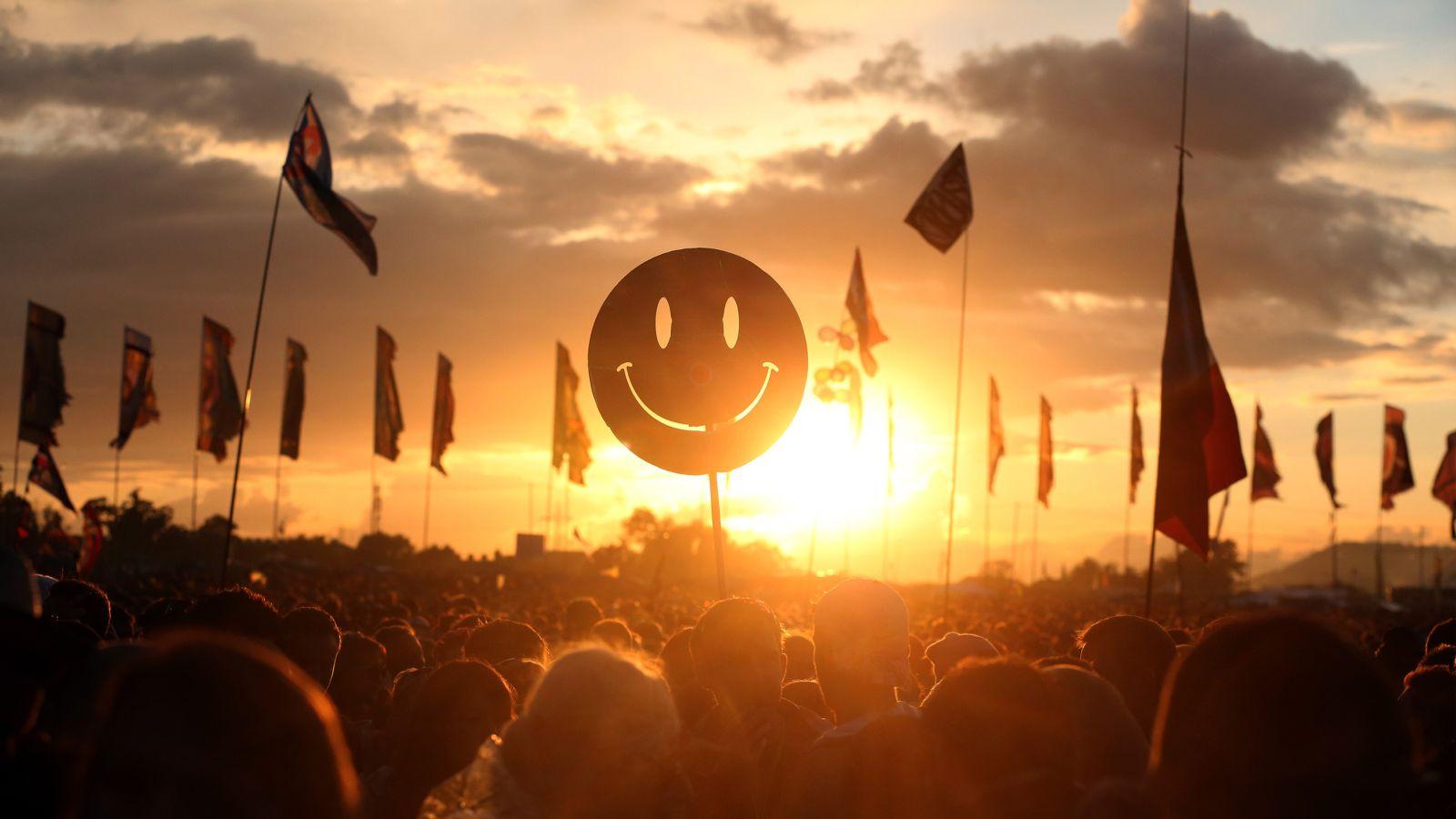 A crowd holding aloft a smiling face emoji.