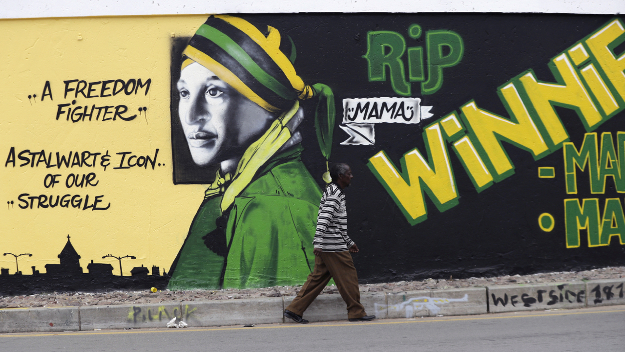 A pedestrian passes a wall mural dedicated to anti-apartheid icon Winnie Madikizela-Mandela on the eve of her burial in Soweto, South Africa, Friday, April 13, 2018. Mandela died April 2, 2018, at the age of 81. (AP Photo/Themba Hadebe)