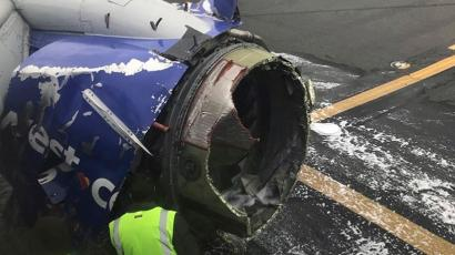 The engine on a Southwest Airlines plane is inspected as it sits on the runway at the Philadelphia International Airport after it made an emergency landing in Philadelphia, Tuesday, April 17, 2018. (Amanda Bourman via AP)