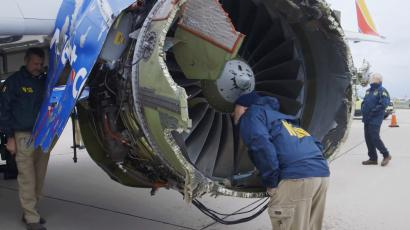 """In this Tuesday, April 17, 2018 frame from video, a National Transportation Safety Board investigator examines damage to the engine of the Southwest Airlines plane that made an emergency landing at Philadelphia International Airport in Philadelphia. A preliminary examination of the blown jet engine of the Southwest Airlines plane that set off a terrifying chain of events and left a businesswoman hanging half outside a shattered window showed evidence of """"metal fatigue,"""" according to the National Transportation Safety Board. (NTSB via AP)"""