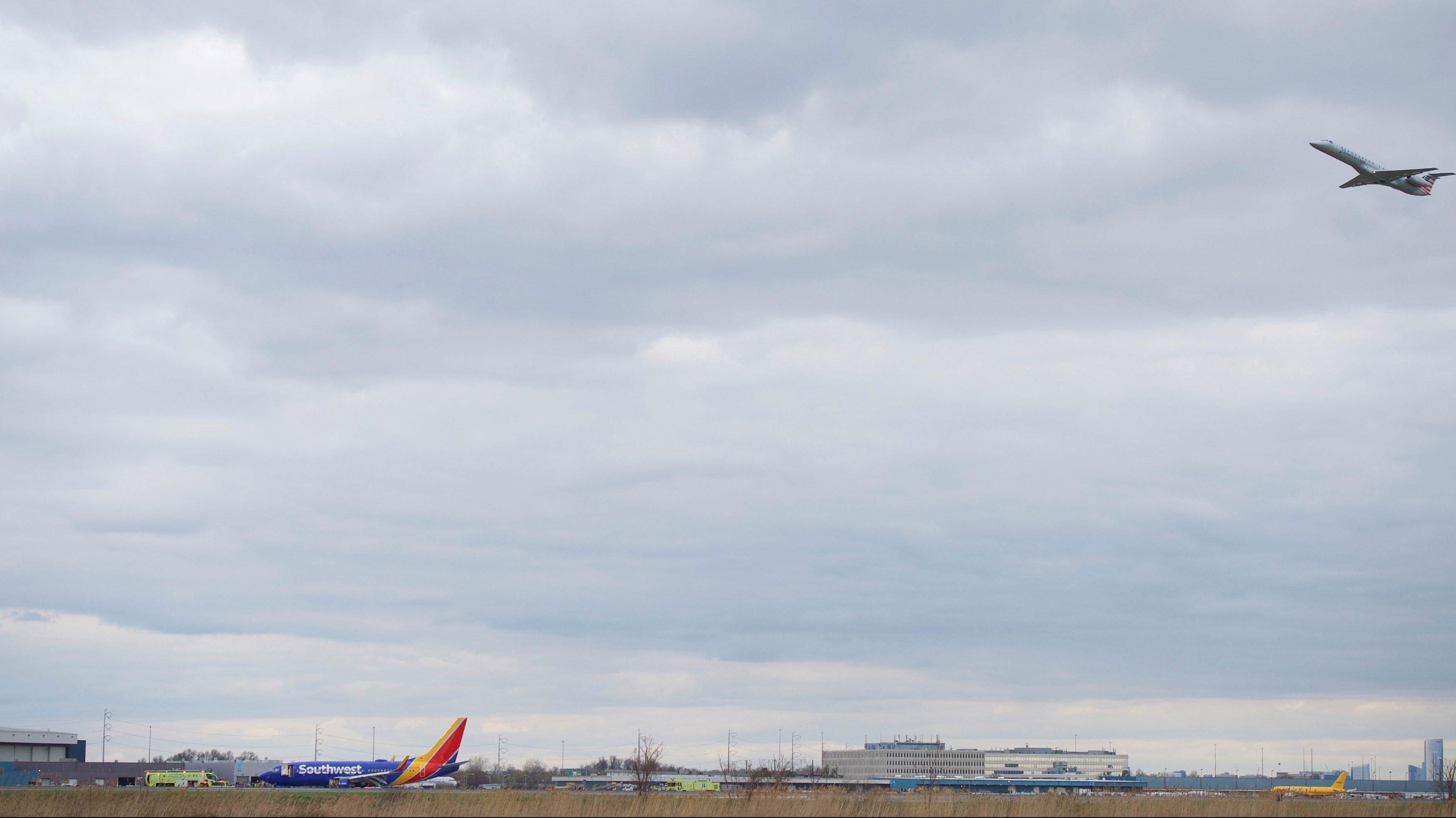 A plane departs as emergency personnel monitor the damaged engine of Southwest Airlines Flight 1380, which diverted to the Philadelphia International Airport this morning, in Philadelphia, Pennsylvania