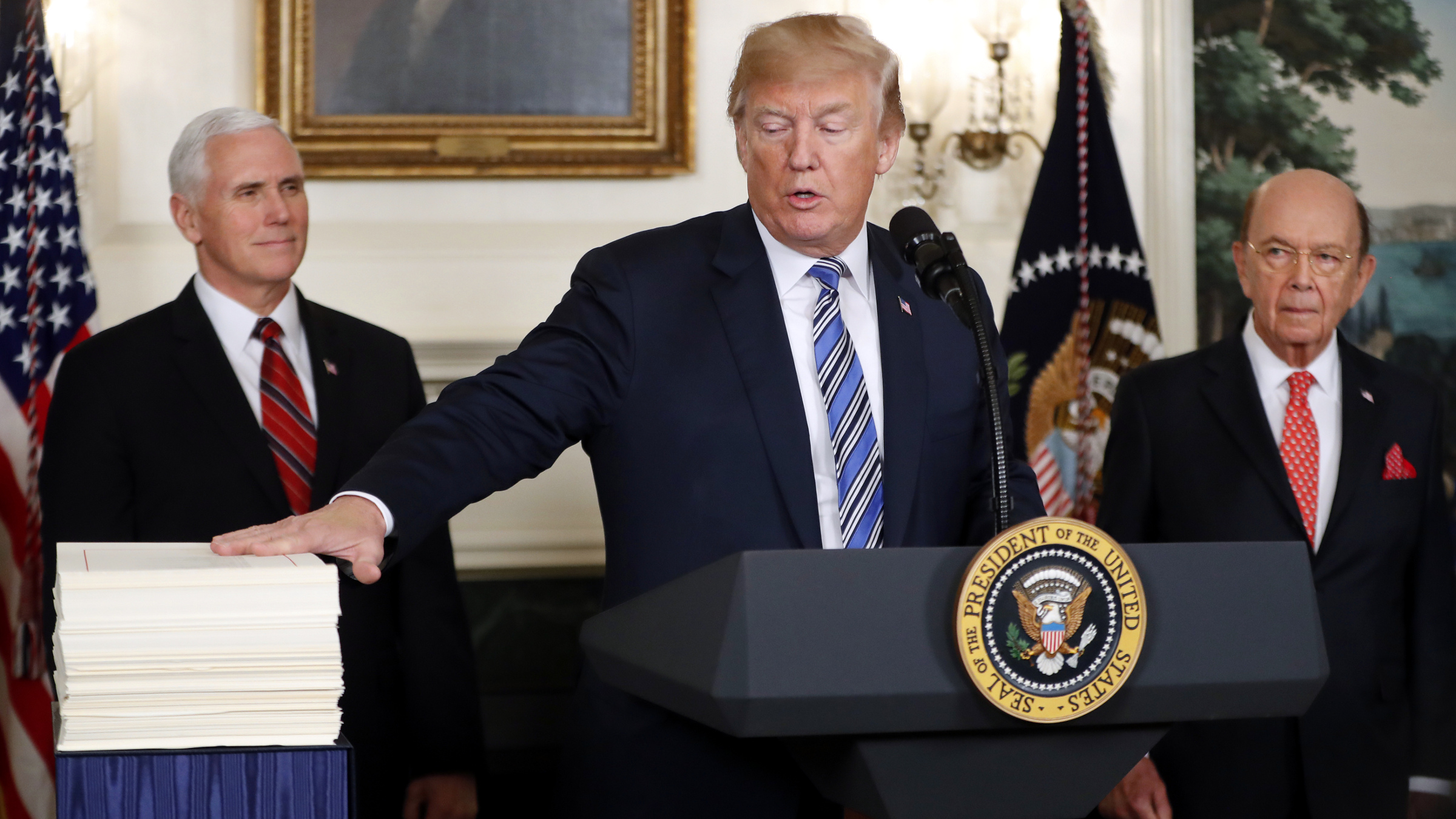 President Donald Trump reaches to touch a copy of the $1.3 trillion spending bill as he speaks in the Diplomatic Room of the White House in Washington, Friday, March 23, 2018. With Trump are Vice President Mike Pence, left, and Commerce Secretary Wilbur Ross.