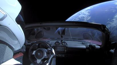 A Tesla roadster hangs in space above the earth after being launched by a SpaceX Falcon Heavy rocket.