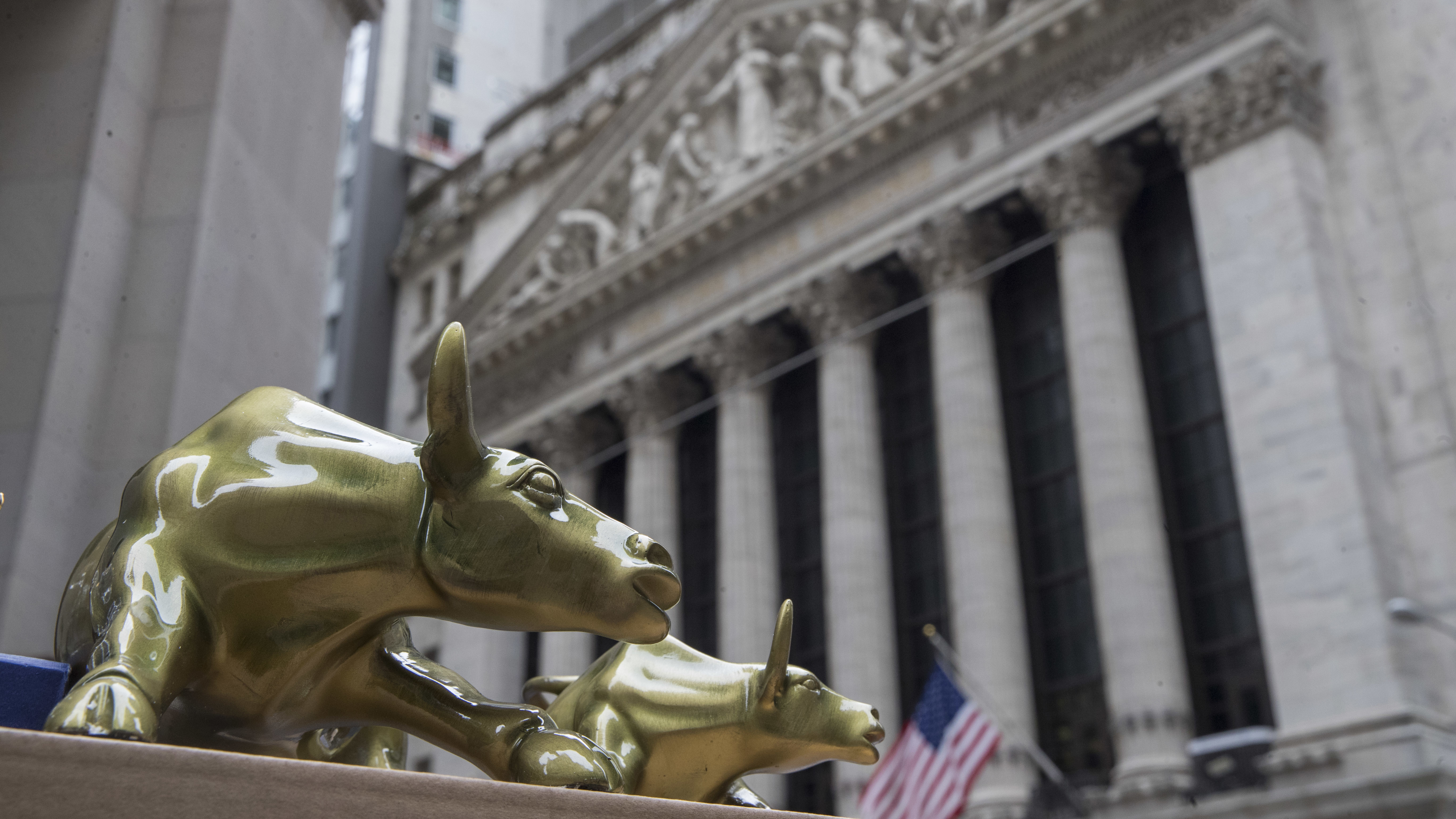 """Replicas of Arturo Di Modica's """"Charging Bull"""" are for sale on a street vendor's table outside the New York Stock Exchange, Tuesday, April 24, 2018, in New York. Stocks are closing sharply lower on Wall Street as big technology and industrial companies take heavy losses. (AP Photo/Mary Altaffer)"""