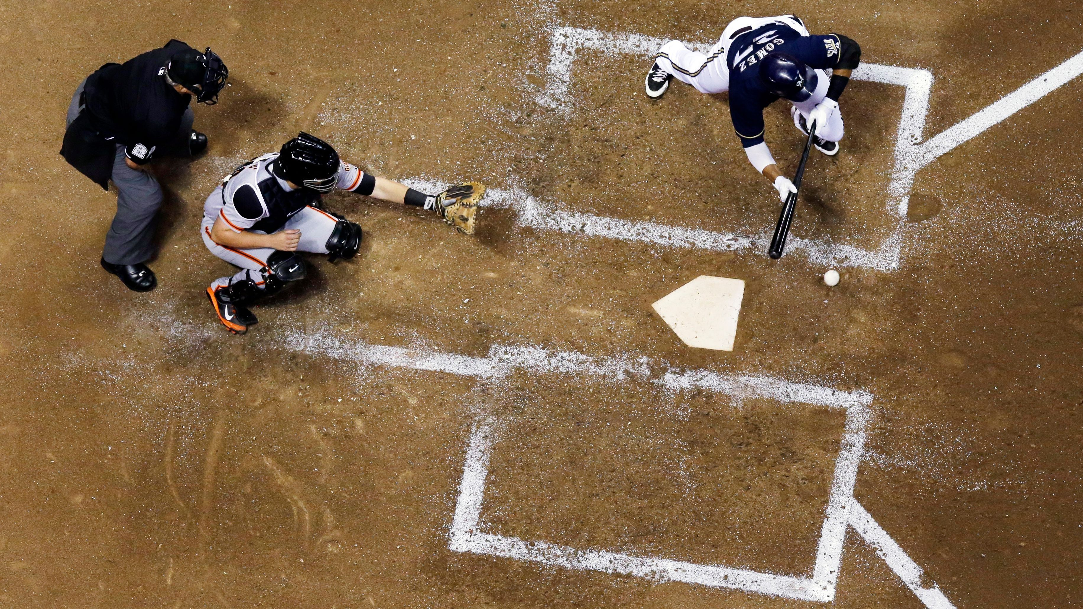 Milwaukee Brewers' Carlos Gomez bunts for a squeeze play during the fifth inning of a baseball game against the San Francisco Giants Tuesday, Aug. 5, 2014.