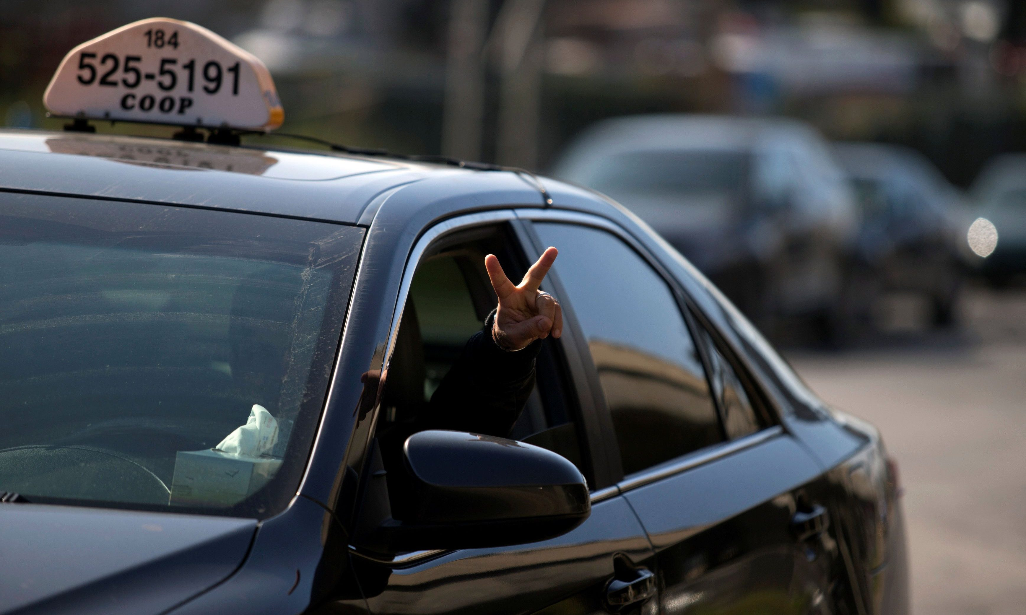 A taxi driver flashes a peace sign as he and other taxi drivers begin their protest against Uber in Montreal...