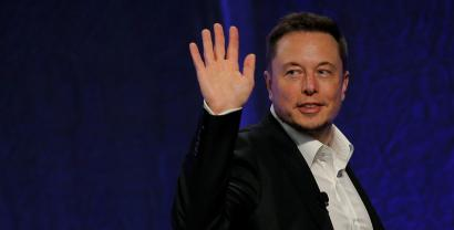 Tesla Motors CEO Elon Musk waves as he leaves a stage after speaking