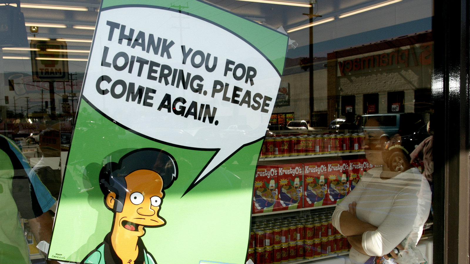 "A poster with ""The Simpsons"" character Apu Nahasapeemapetilon, Jr., proprietor of the Springfield Kwik-E-Mart, is displayed on the window of a 7-Eleven convenience store in Burbank, California, July 2, 2007. The store was converted into a ""Kwik-E- Mart"", made famous by the popular animated television program. Specially themed products from the show, such as cans of Buzz cola and Krusty-O's cereal, were on sale."