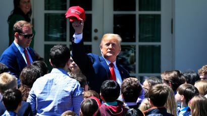 "President Donald Trump surrounded by children of journalists and White House staff waves, a Make America Great Again cap, on the Rose Garden in celebration of ""Bring Our Daughters and Sons to Work Day"" at the White House in Washington, Thursday, April 26, 2018. (AP Photo/Manuel Balce Ceneta)"