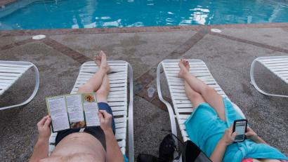 A couple lounges on deck chairs by the pool. The woman is reading on her phone.