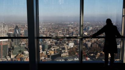 A woman looks out at the financial district from a window in The View gallery at the Shard, in London
