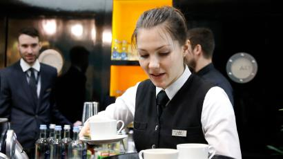 A waitress works at the bar on the stand of Hyatt Hotels