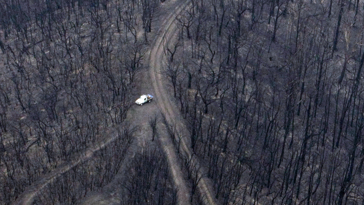 A vehicle is seen near the remains of a house destroyed by bushfires is seen in the town of Kinglake, 55km (34 miles) northeast of Melbourne February 8, 2009. Australian bushfires have killed 76 people and burnt hundreds of homes in the worst fire disaster in three decades, as a heatwave and strong winds sent sheets of flame racing through towns and farmland near Melbourne.