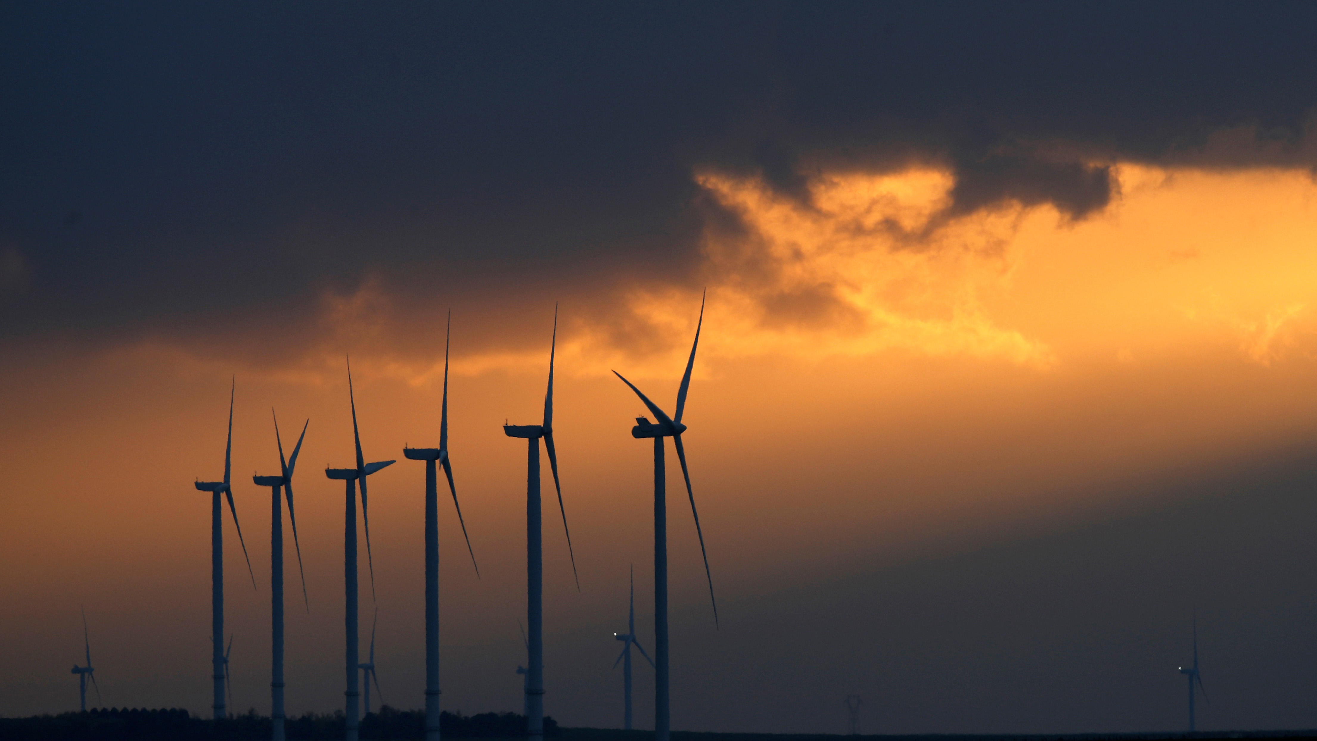 Power-generating windmill turbines are seen during sunset at a wind park near Reims, France, November 13, 2017. REUTERS/Christian Hartmann - RC1406F2E060