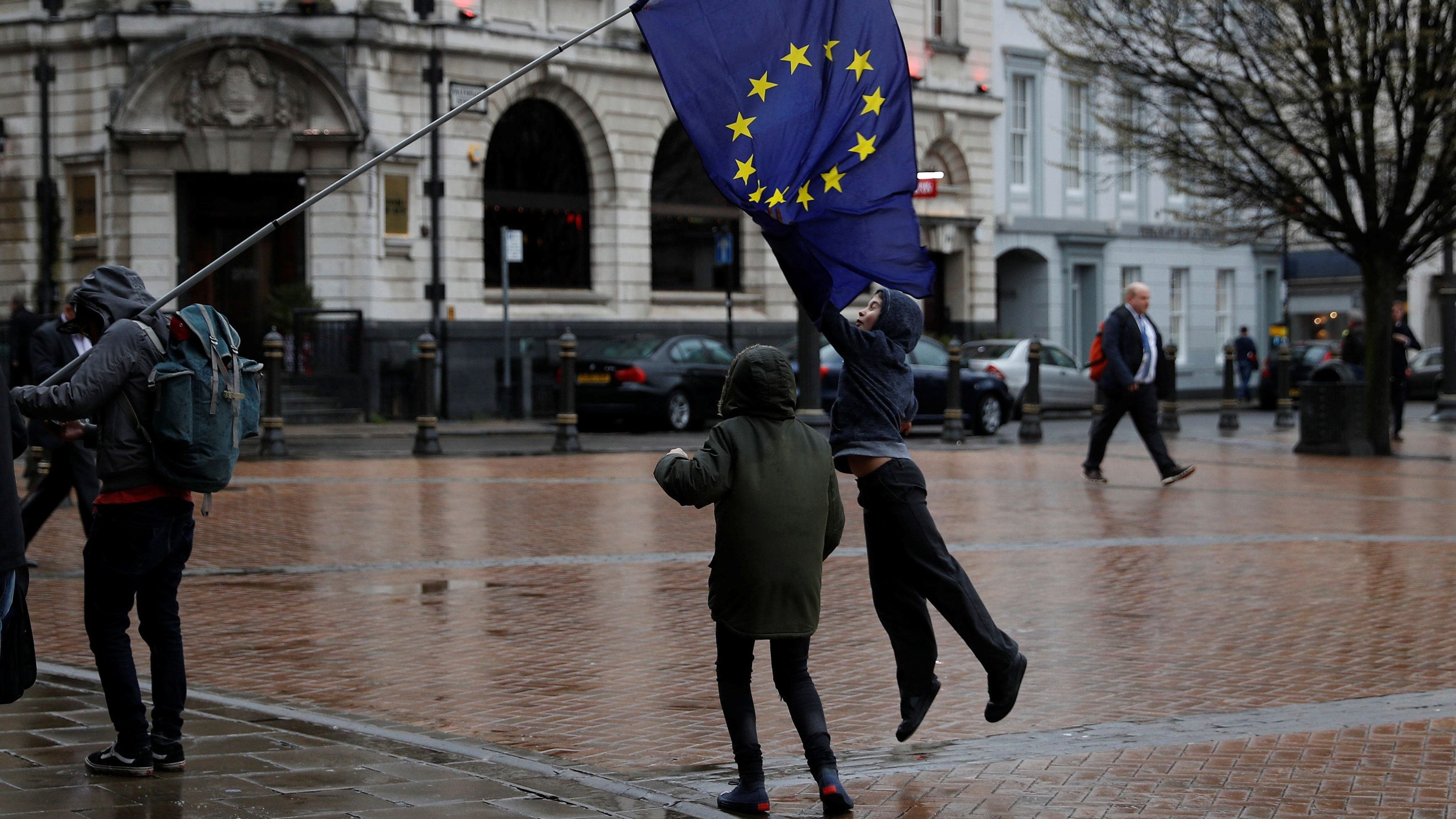 Children jump up to grab a European Union flag during an anti-Brexit demonstration after Britain's Prime Minister Theresa May triggered the process by which the United Kingdom will leave the Euopean Union, in Birmingham