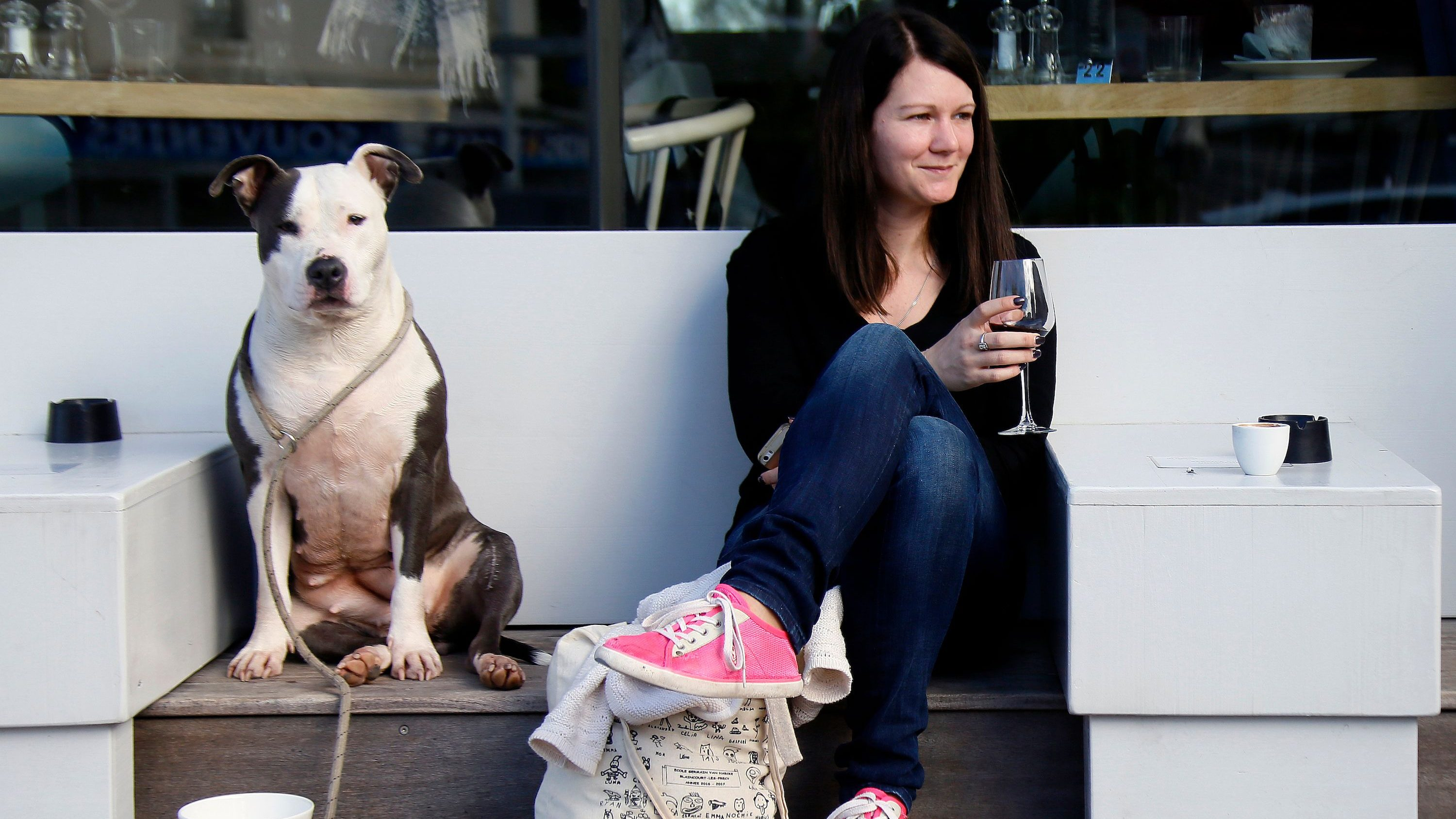 Emilie Liger, from Biarritz, drinks a glass of red wine accompanied by her dog Lara at the terrace of a restaurant in Biarritz, southwestern France, Thursday, Fev.15, 2018. Temperatures in southwestern France reached 19 degrees Celsius (66,2 Fahrenheit).