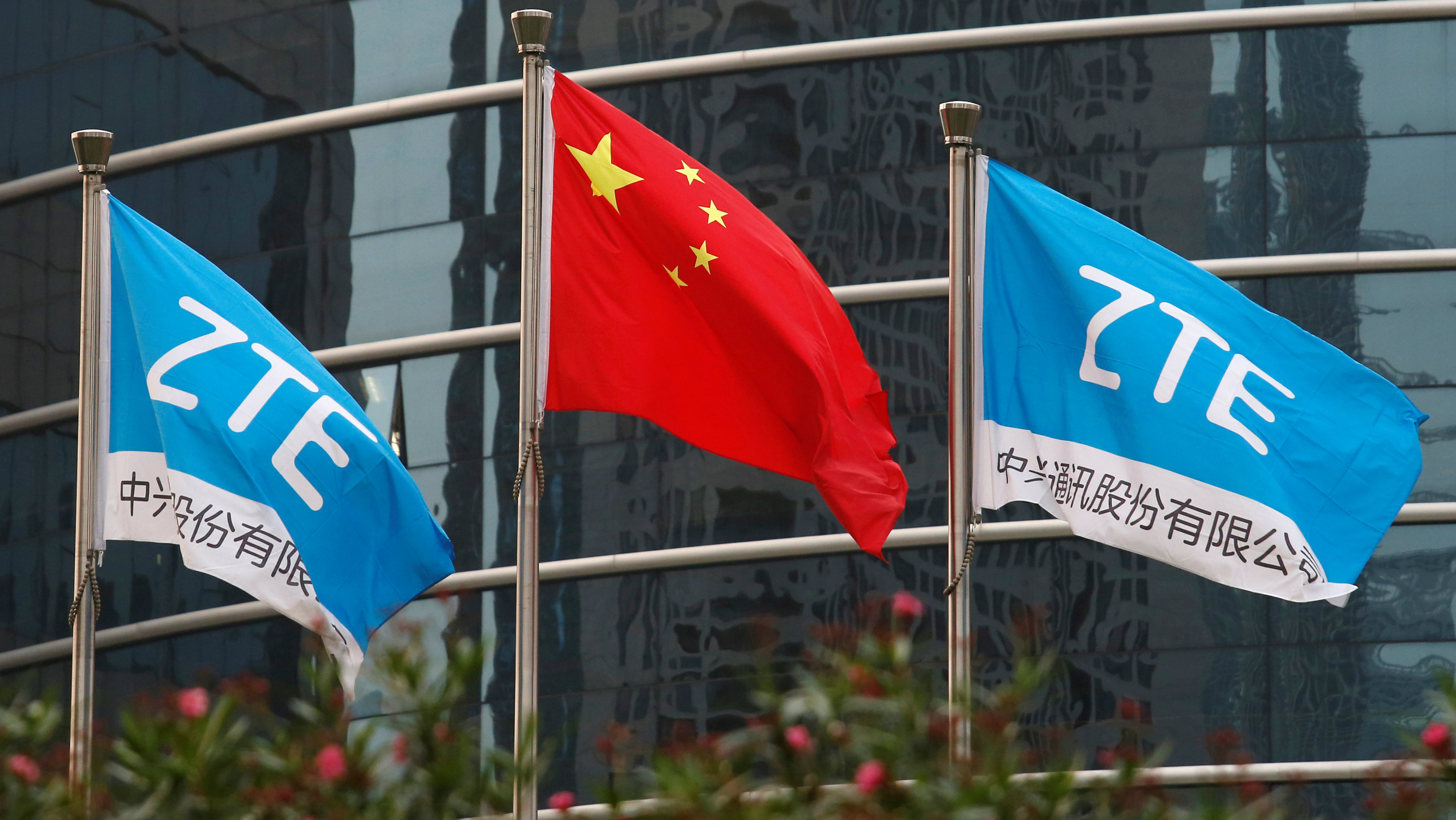A Chinese national flag and two flags bearing the name of ZTE fly outside the ZTE R&D building in Shenzhen