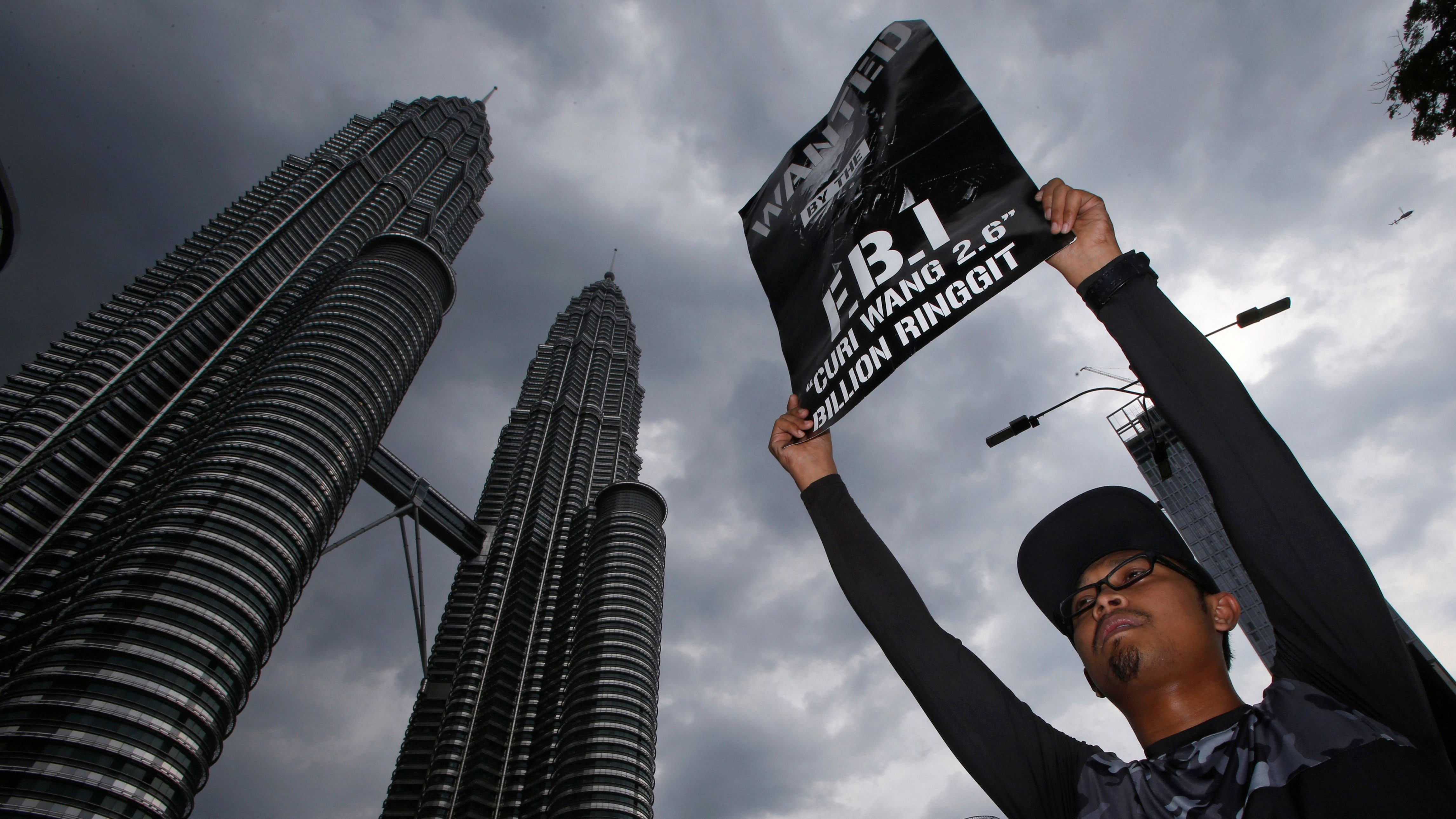 A man holds up a poster during a 1MDB protest organized by Pro-democracy group Bersih, calling for Malaysian Prime Minister Najib Abdul Razak to resign, in Kuala Lumpur, Malaysia November 19, 2016.