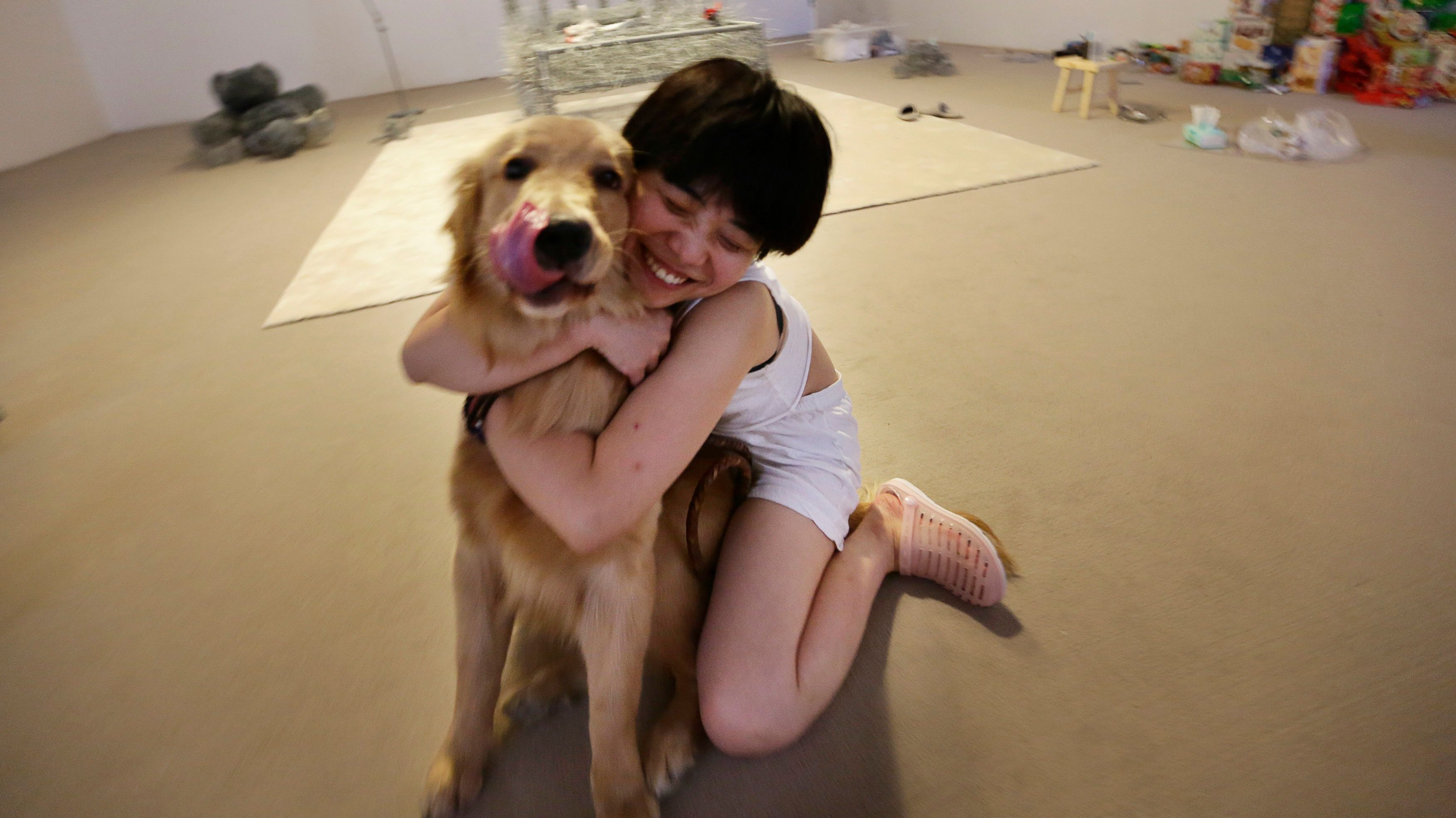 "Chinese artist Zhou Jie hugs her pet dog Dan Dan, which visited her, at Beijing Art Now Gallery, in Beijing August 11, 2014. Zhou started her art project titled ""36 Days"" on August 9, in which she would live inside an exhibition hall with an unfinished iron wire bed, some iron wire sculptures in the shape of stuffed animal dolls, a certain amount of food and her mobile phone for 36 days. According to Zhou, the entire process is open to visitors and she may also interact with them. Picture taken August 11, 2014."