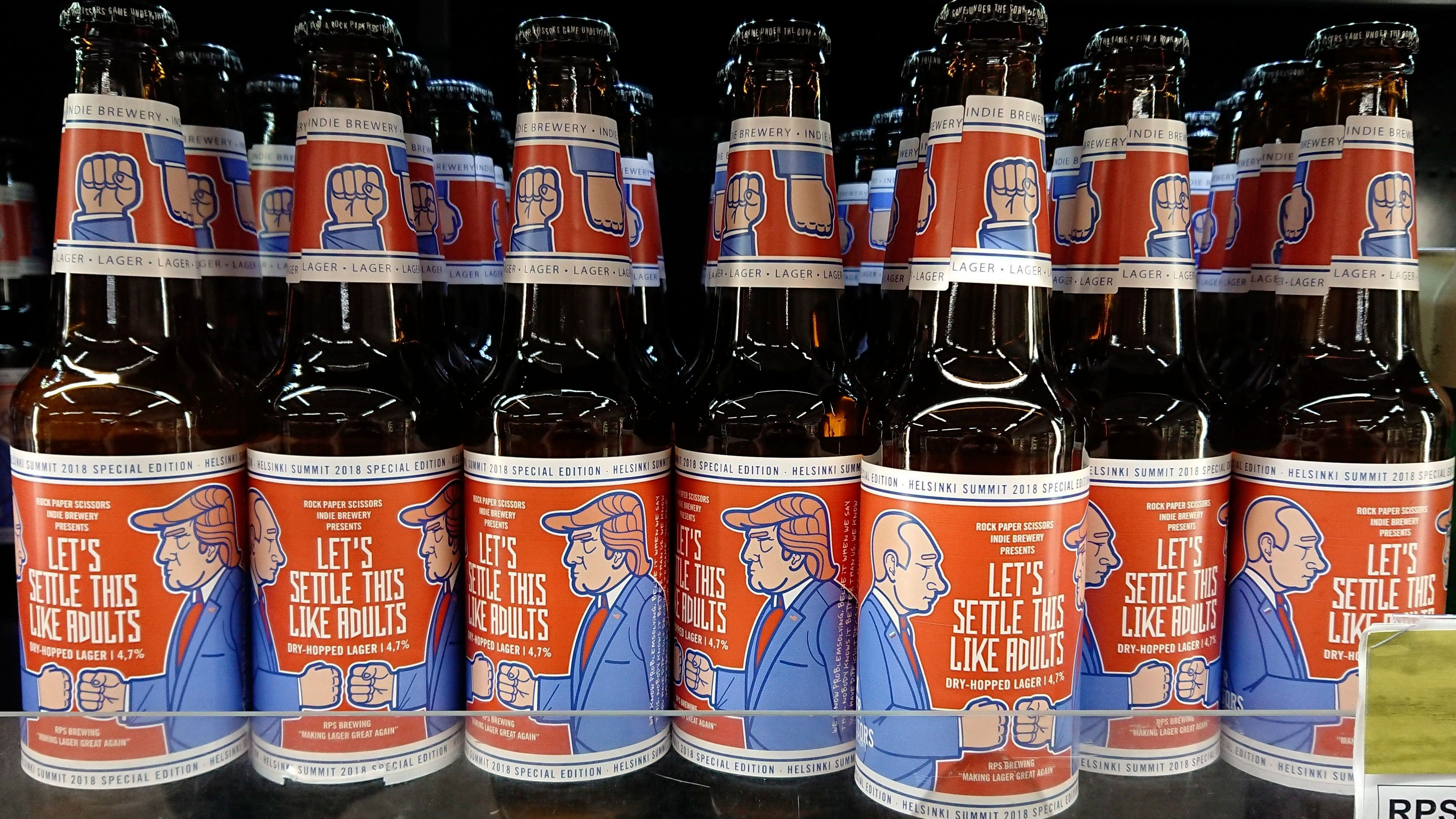 """The label of Finnish beer brewery Rock Paper Scissors shows a cartoon of Russian President Vladimir Putin and U.S President Donald Trump, in a grocery store in Helsinki, Wednesday, July 11, 2018. In a combative start to his NATO visit, Trump asserted Wednesday that a pipeline project has made Germany """"totally controlled"""" by and """"captive to Russia"""" and blasted allies' defense spending, opening what was expected to be a fraught summit with a list of grievances involving American allies. (Aku H'yrynen/Lehtikuva via AP)"""