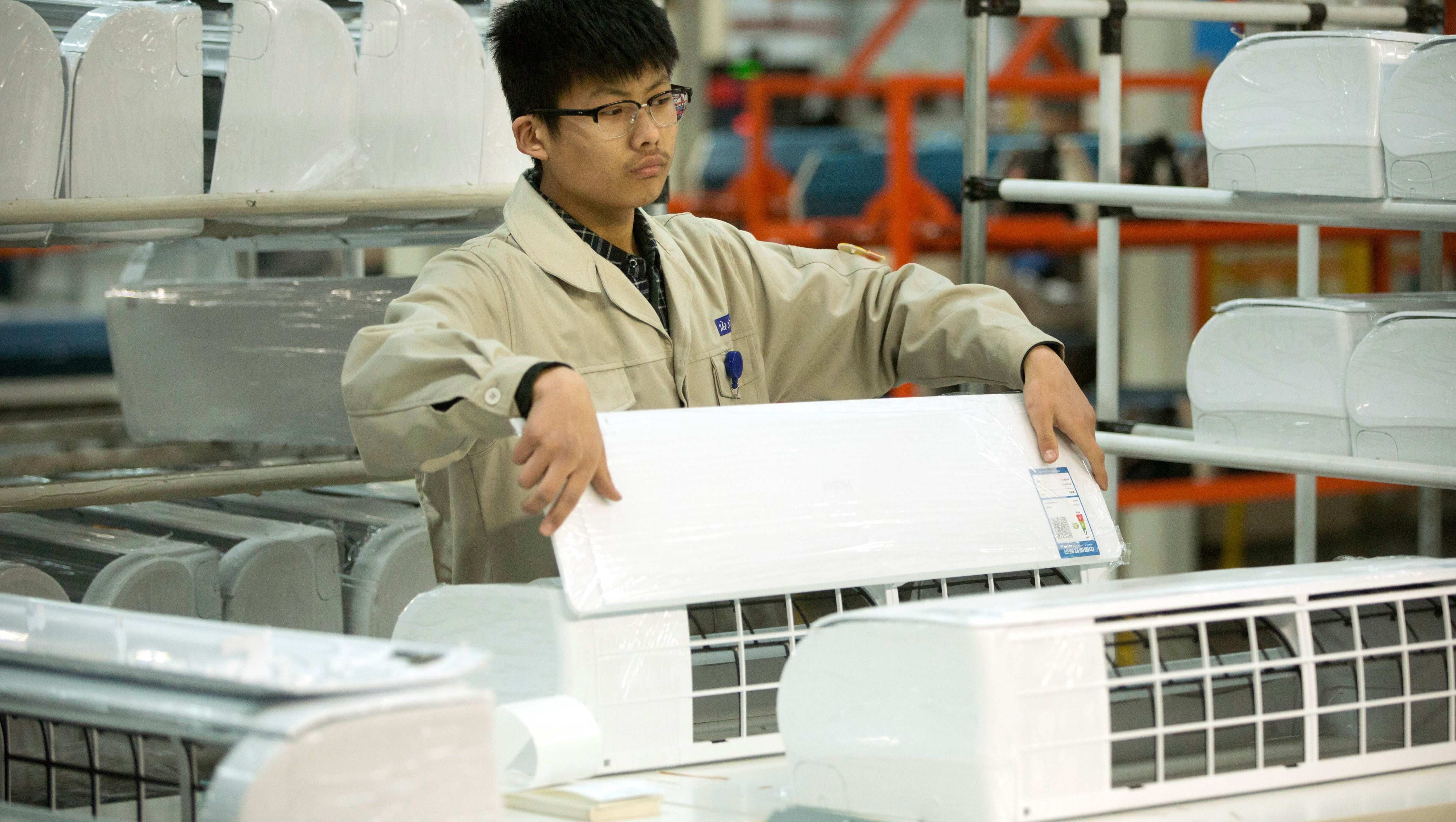 A factory worker in China assembles an AC.