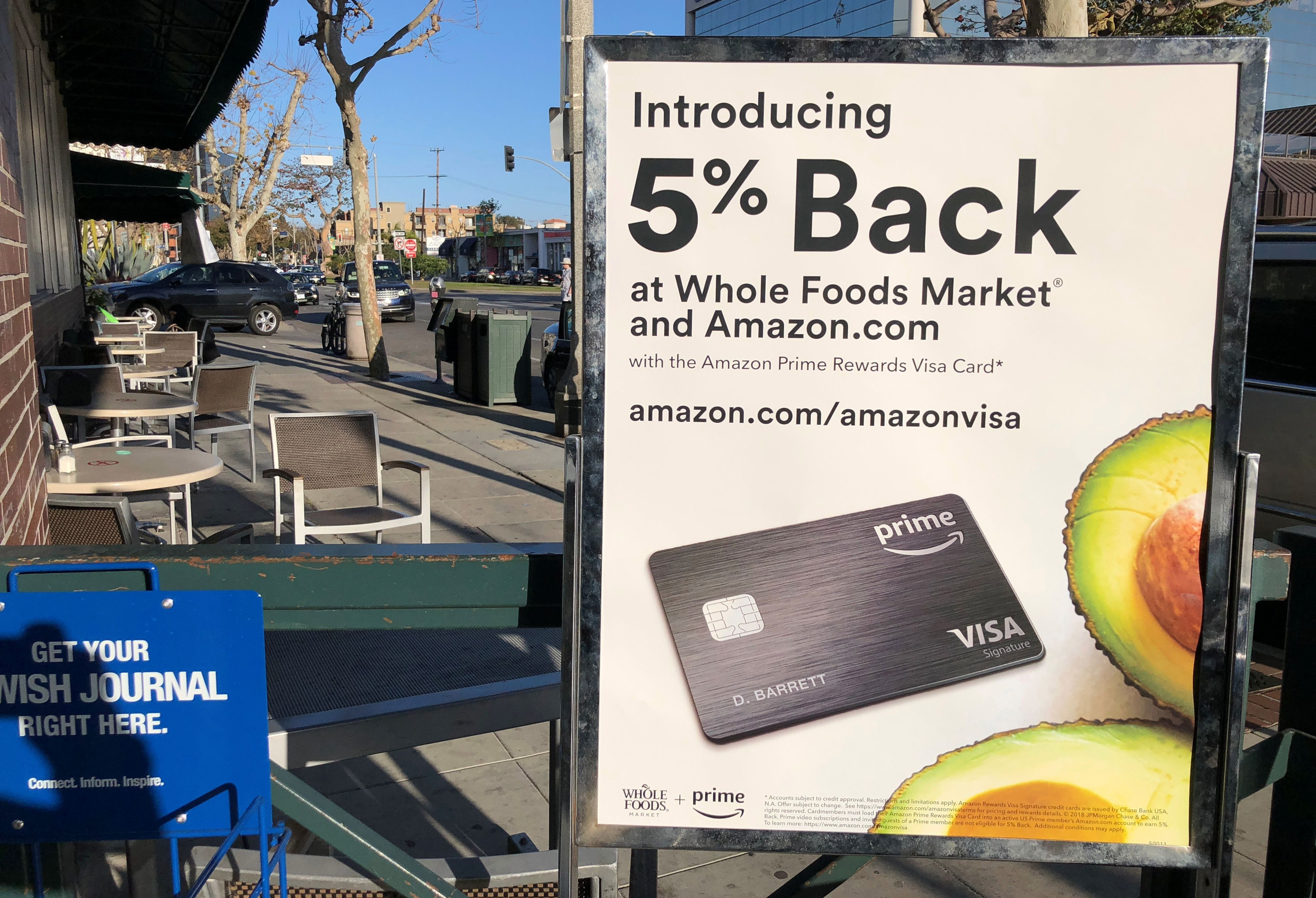 A sign advertising a credit card offering a discount at Whole Foods and Amazon is seen outside a Whole Foods store in Los Angeles, California, U.S., February 26, 2018. Picture taken February 26, 2018. REUTERS/Lucy Nicholson - RC1E9B62E220