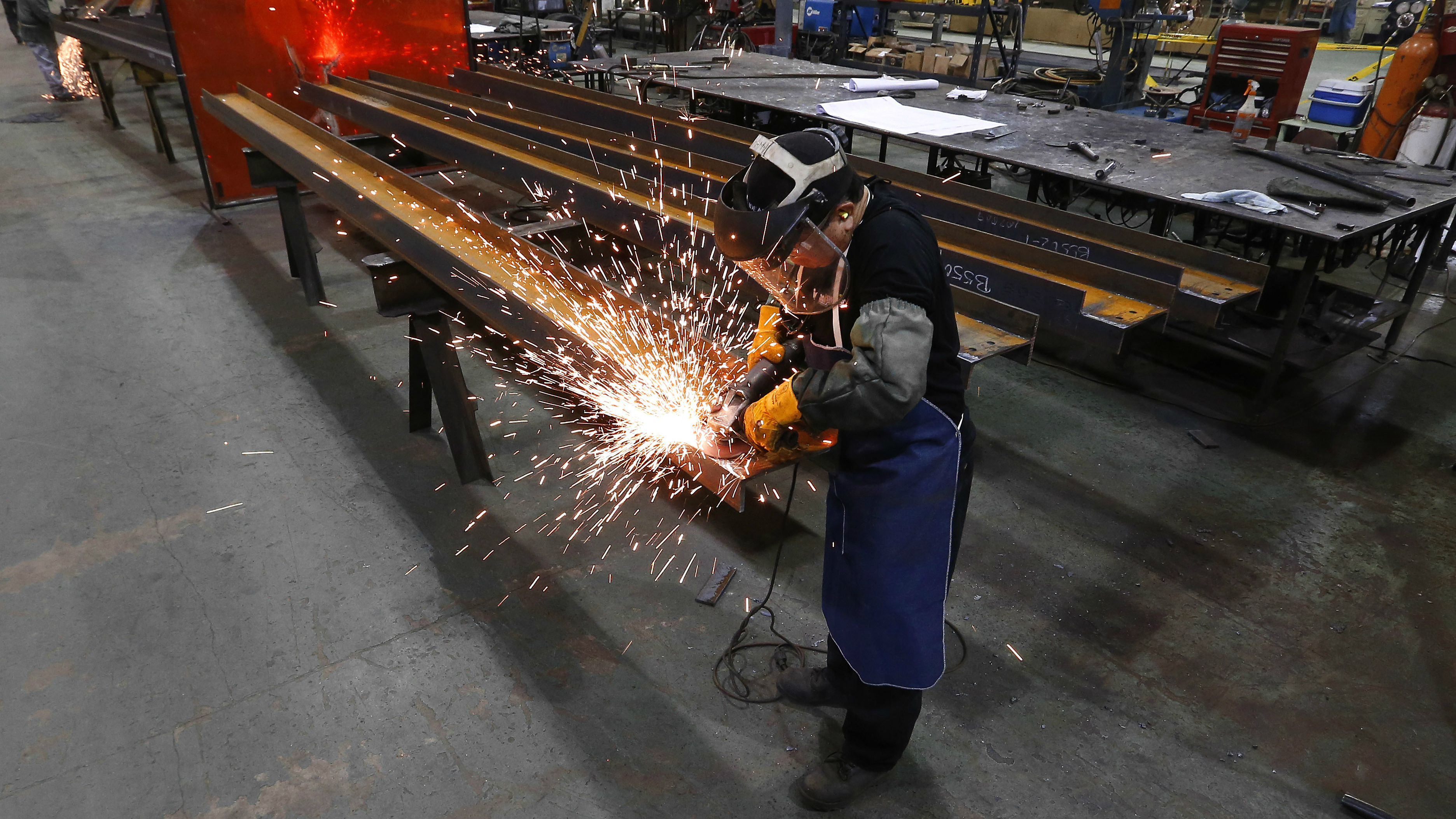 In this Jan. 23, 2014 file photo, Jesus Rodriguez grinds steel at the IDEAL Group in Detroit. Factory orders dropped 2.4 percent after a 2.8 percent rise in October, the Commerce Department reported Friday, Jan. 6, 2017. (AP Photo/Paul Sancya)