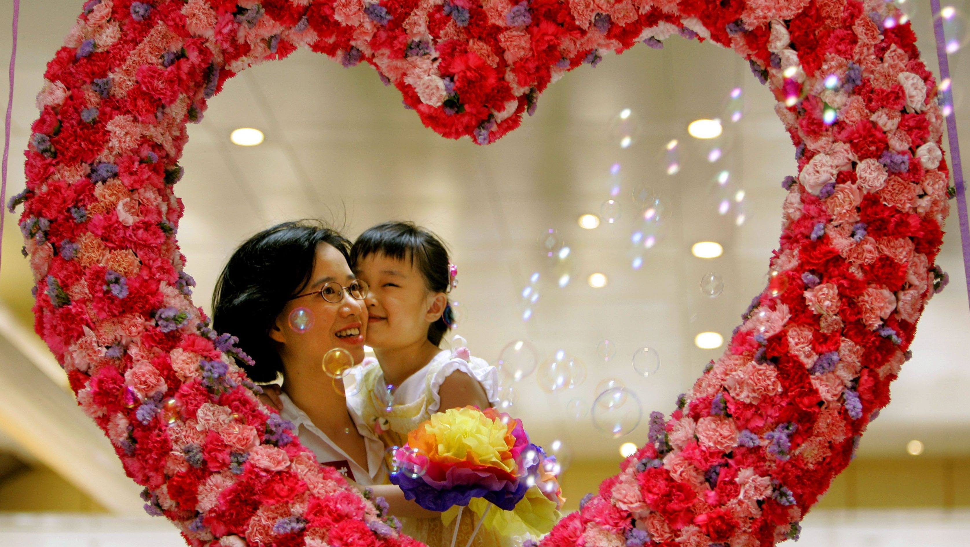 A mother, Beatrice Watt, poses with her daughter Whitney Watt behind a heart shape decoration assembled by 1,000 carnations as celebrating the upcoming mother's day in Hong Kong on May 11, 2006.