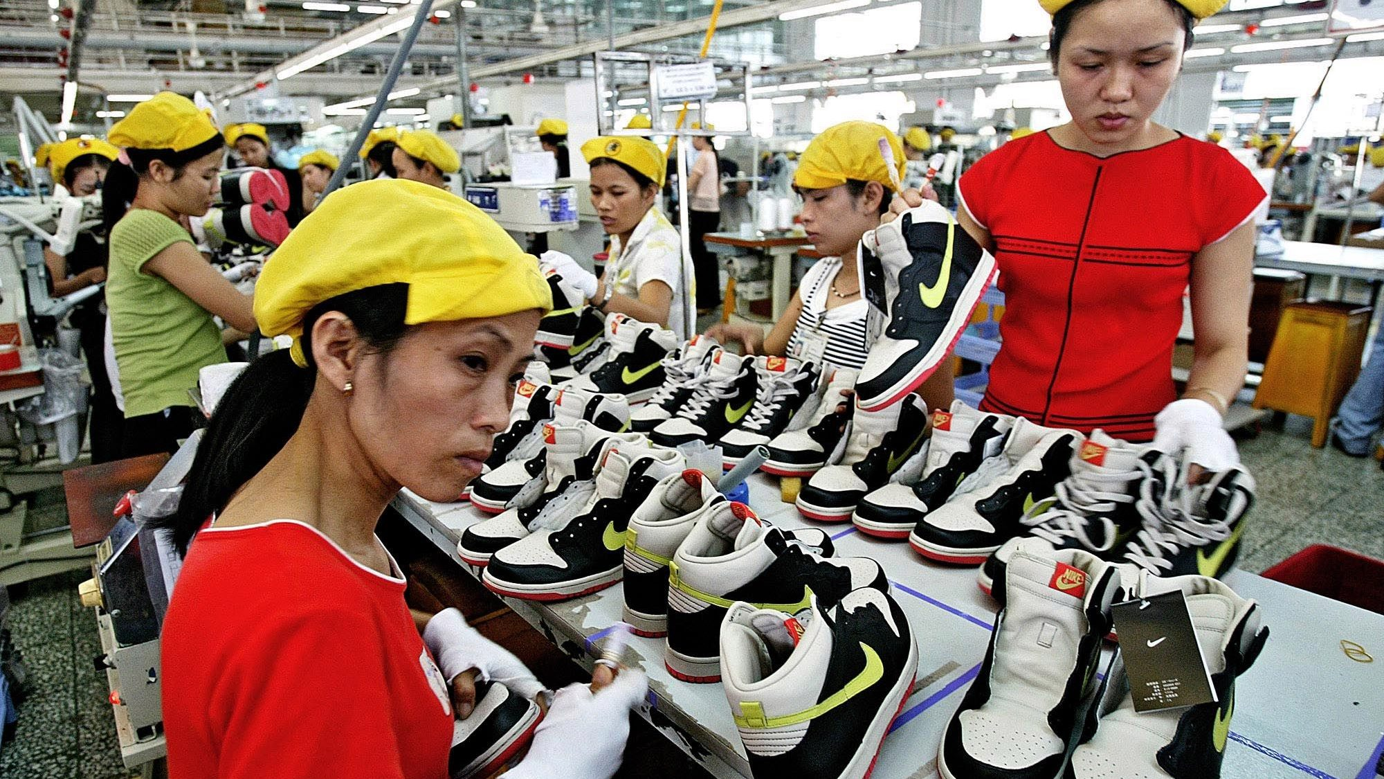 **FILE** Vietnamese workers put the finishing touches on a production line making athletic shoes at the Nike factory on the outskirts of Ho Chi Minh City, formerly Saigon