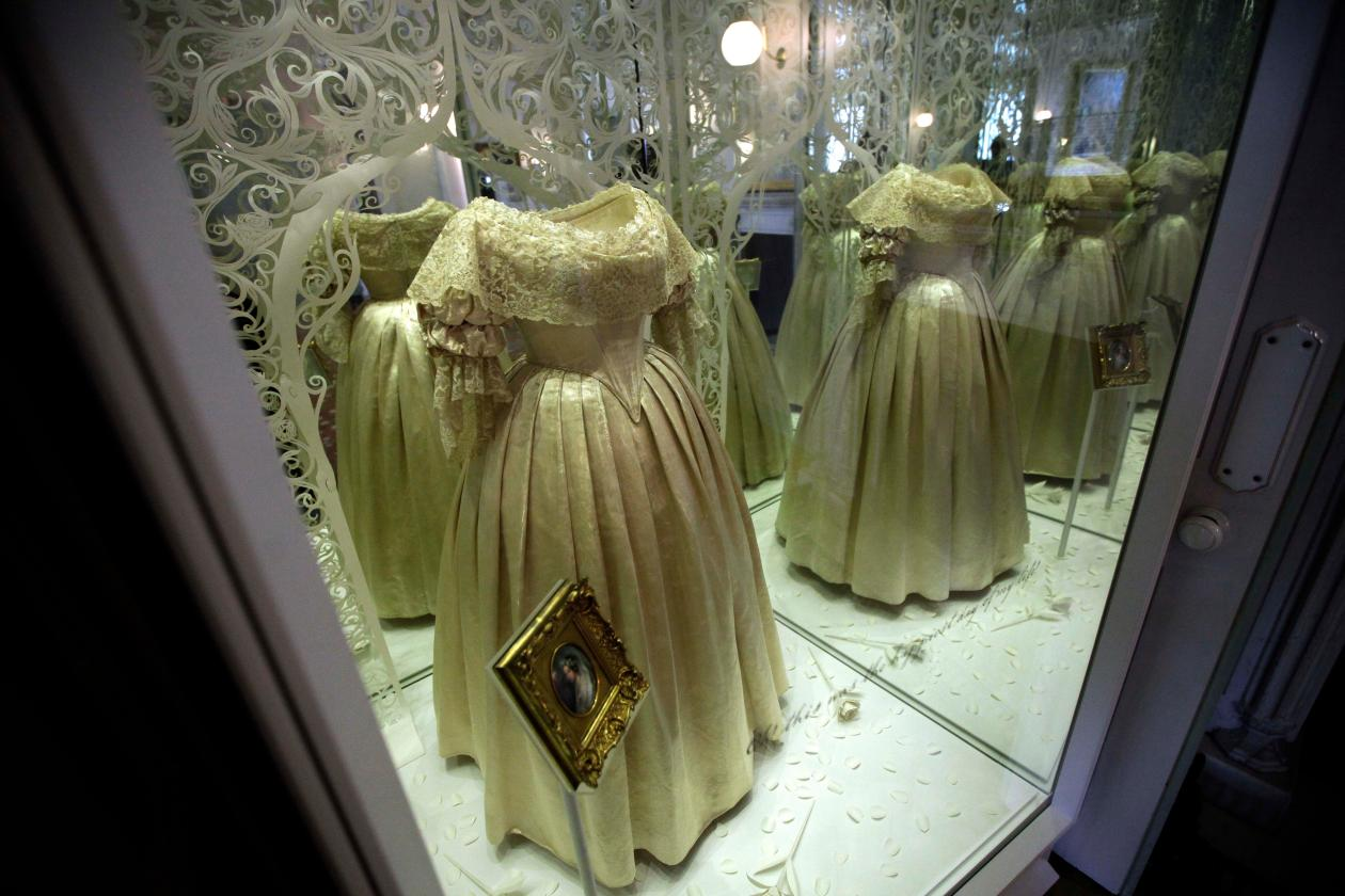 """The ivory silk wedding dress worn by Queen Victoria in her marriage to Prince Albert in 1840 is displayed and then reflected in mirrors as part of the exhibition """"Victoria Revealed"""" in the building where she was born, Kensington Palace in London, Tuesday, March 20, 2012. Kensington Palace has been transformed following a 12 million pounds ($19 million, 14.4 million euro) restoration project timed to be completed for this summer's Queen Elizabeth II's Diamond Jubilee and the London 2012 Olympics. (AP Photo/Matt Dunham)"""