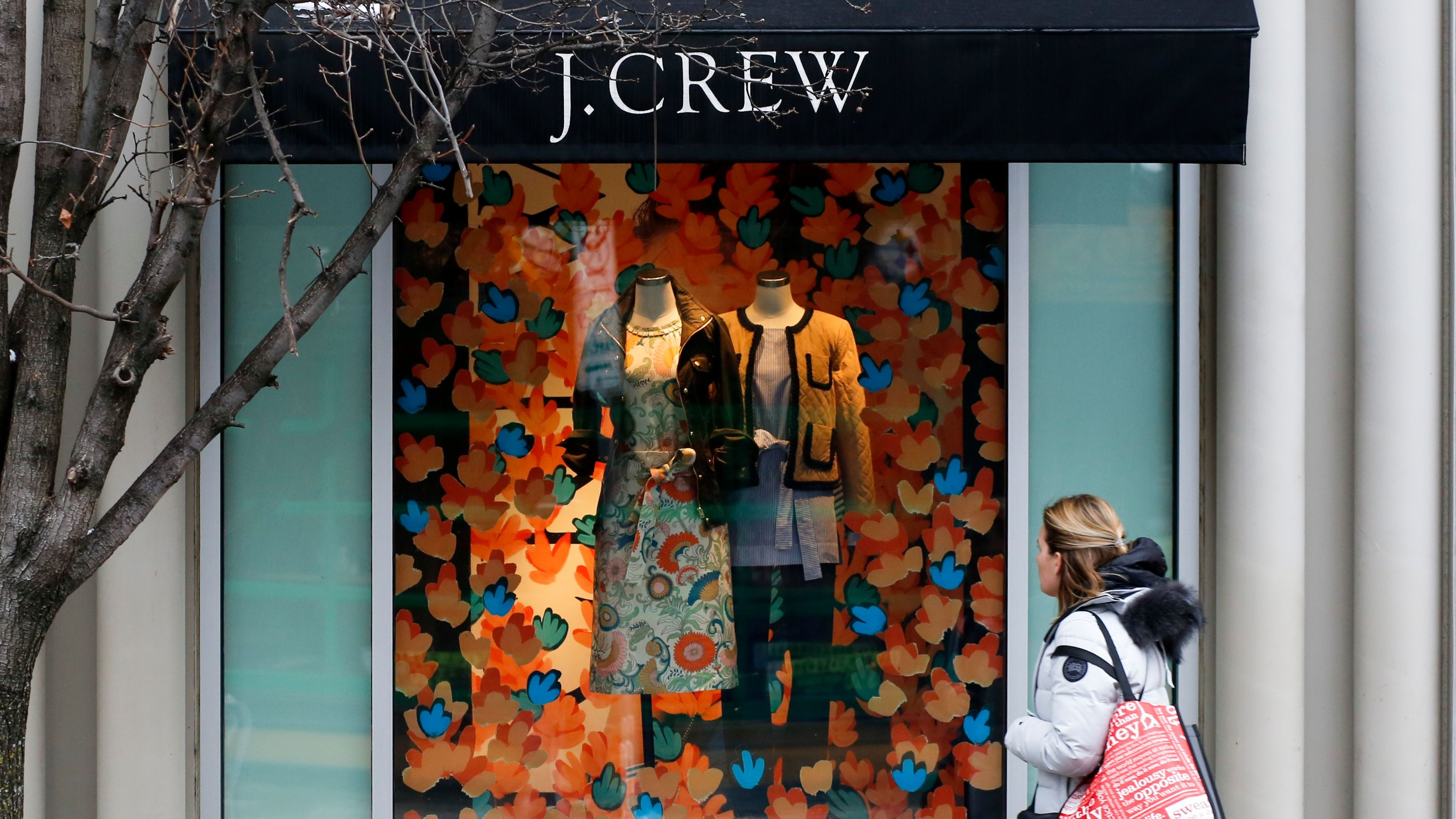 In this Friday, Feb. 10, 2017, photo, a shopper passes a display in the window of a J. Crew store in the Shadyside shopping district of Pittsburgh. On Wednesday, March 15, 2017, the Commerce Department releases U.S. retail sales data for February. (AP Photo/Gene J. Puskar)