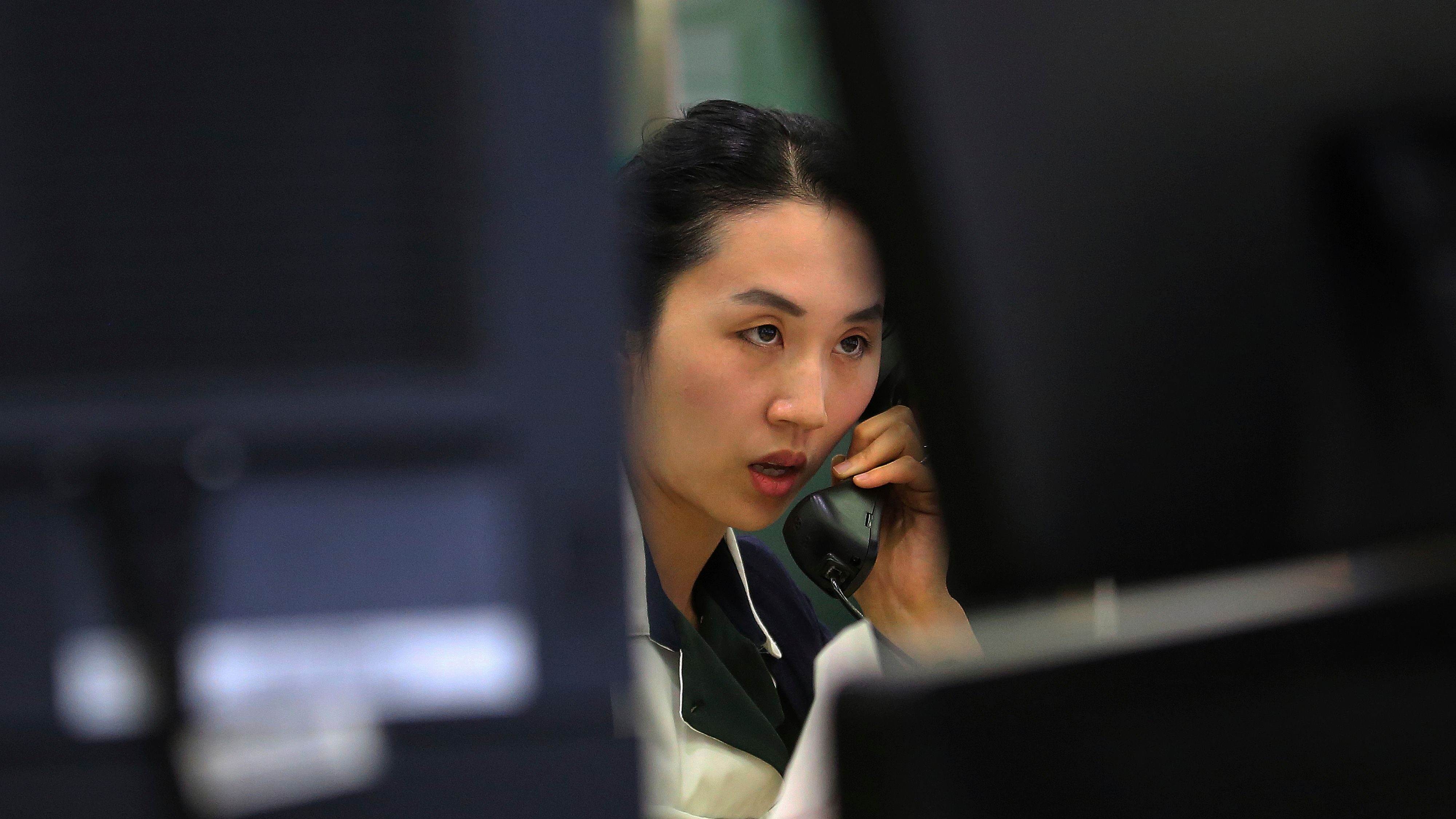A currency trader talks on the phone at the foreign exchange dealing room of the KEB Hana Bank headquarters in Seoul, South Korea, Monday, June 5, 2017. Asian stock markets were mixed on Monday following the London attack over the weekend and a private survey showing improvement in China's service sector. Stocks moved within a narrow range ahead of the week packed with political events and economic data from the United Kingdom's elections to China's export data. (AP Photo/Ahn Young-joon)