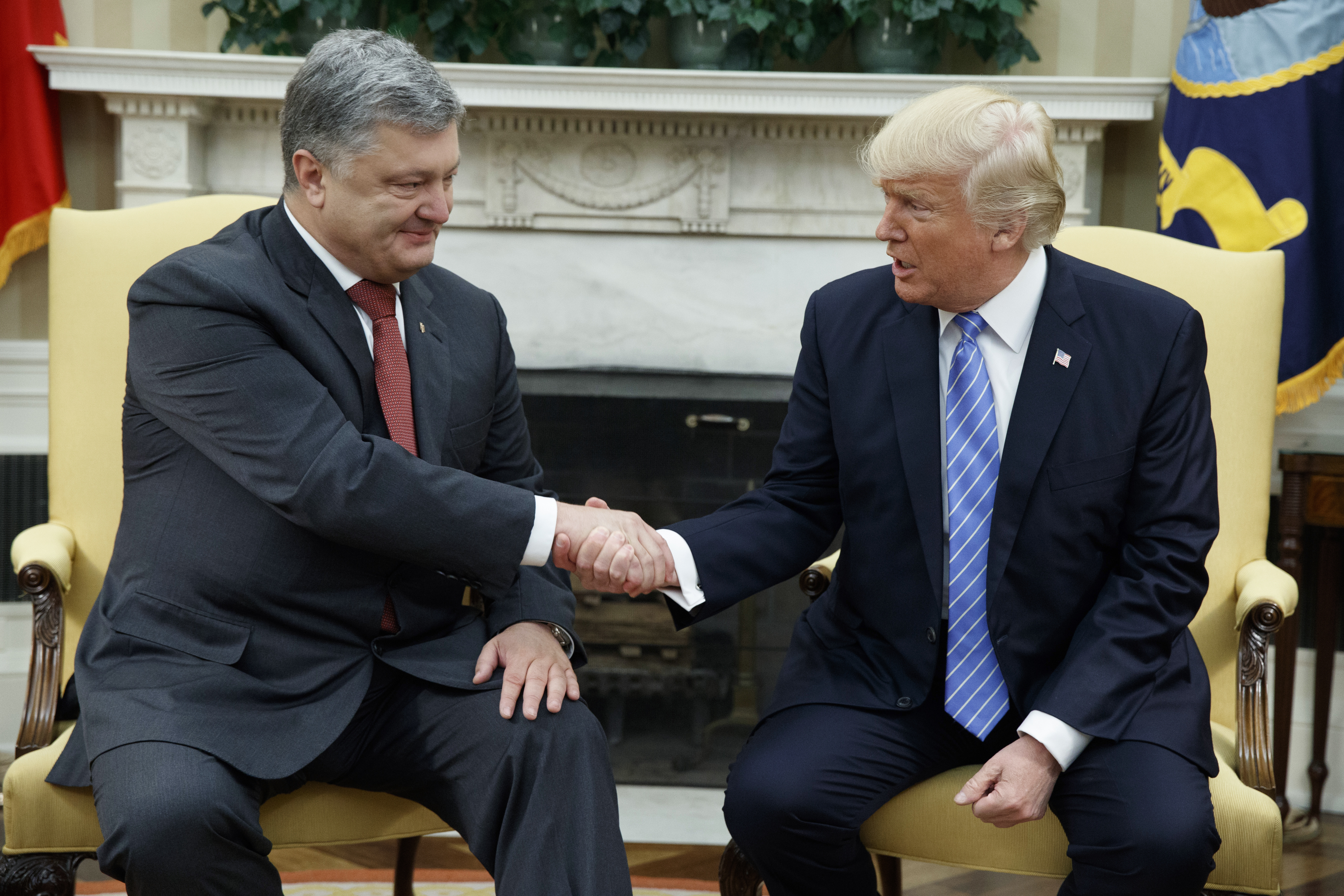 FILE - In this June 20, 2017, file photo, President Donald Trump shakes hands with Ukrainian President Petro Poroshenko during a meeting in the Oval Office of the White House in Washington. Seeking leverage with Russia, the Trump administration has reopened consideration of long-rejected plans to give Ukraine lethal weapons, even if that would plunge the United States deeper into the former Soviet republic's conflict. (AP Photo/Evan Vucci, File)