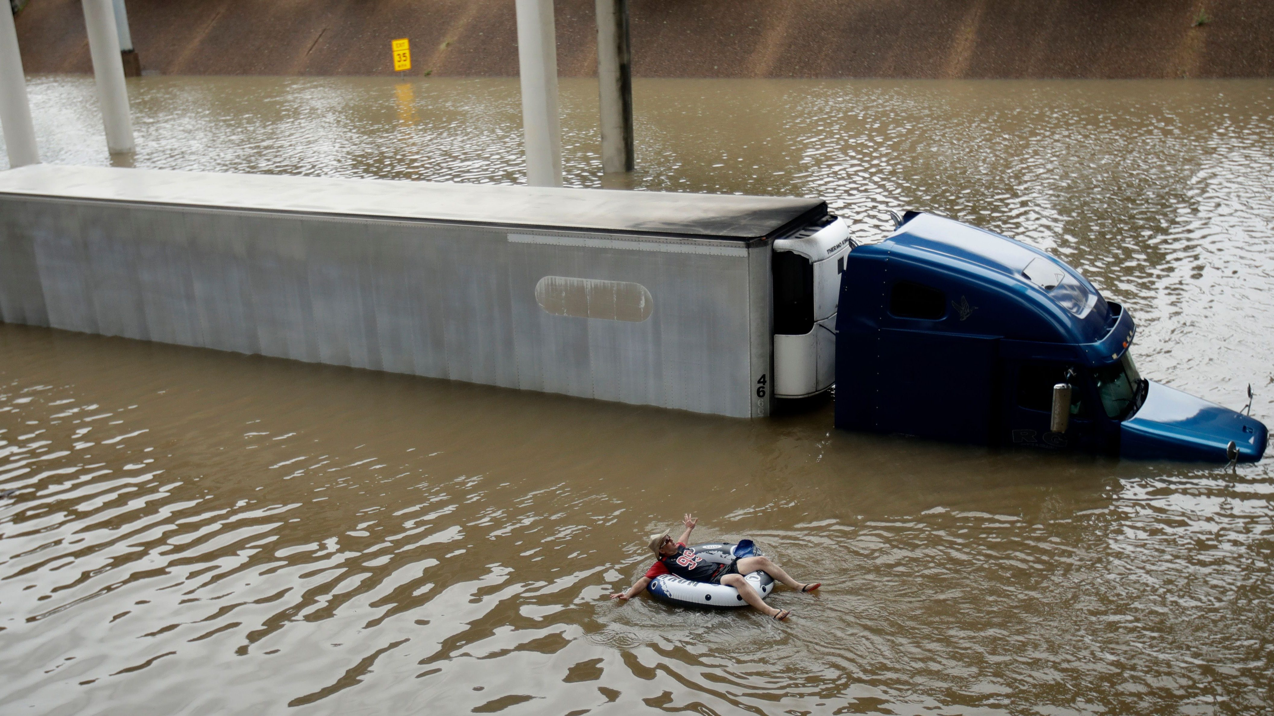 After helping the driver of the submerged truck get to safety, a man floats on the freeway flooded by Tropical Storm Harvey on Sunday, Aug. 27, 2017, near downtown Houston.  (AP Photo/Charlie Riedel)