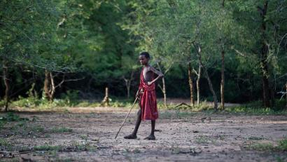 A young Maasai herder boy stands in the bush at the end of the day near Mikumi National Park in Tanzania, Friday, March 23, 2018.
