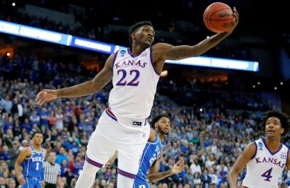 FILE - In this March 25, 2018, file photo, Kansas' Silvio De Sousa reaches for a rebound during the first half of a regional final game against Duke in the NCAA men's college basketball tournament, in Omaha, Neb. Kansas and North Carolina State are the latest schools to be swept up in a bribery scandal involving college basketball. A rewritten indictment released Tuesday, April 10, 2018, in New York alleges that an Adidas representative, who no longer works for the company, arranged for payments to parents of athletes willing to commit to the schools. No players are directly named, but specific details make clear the indictment is describing former North Carolina State star Dennis Smith Jr. and Kansas player Silvio De Sousa.(AP Photo/Charlie Neibergall, File)