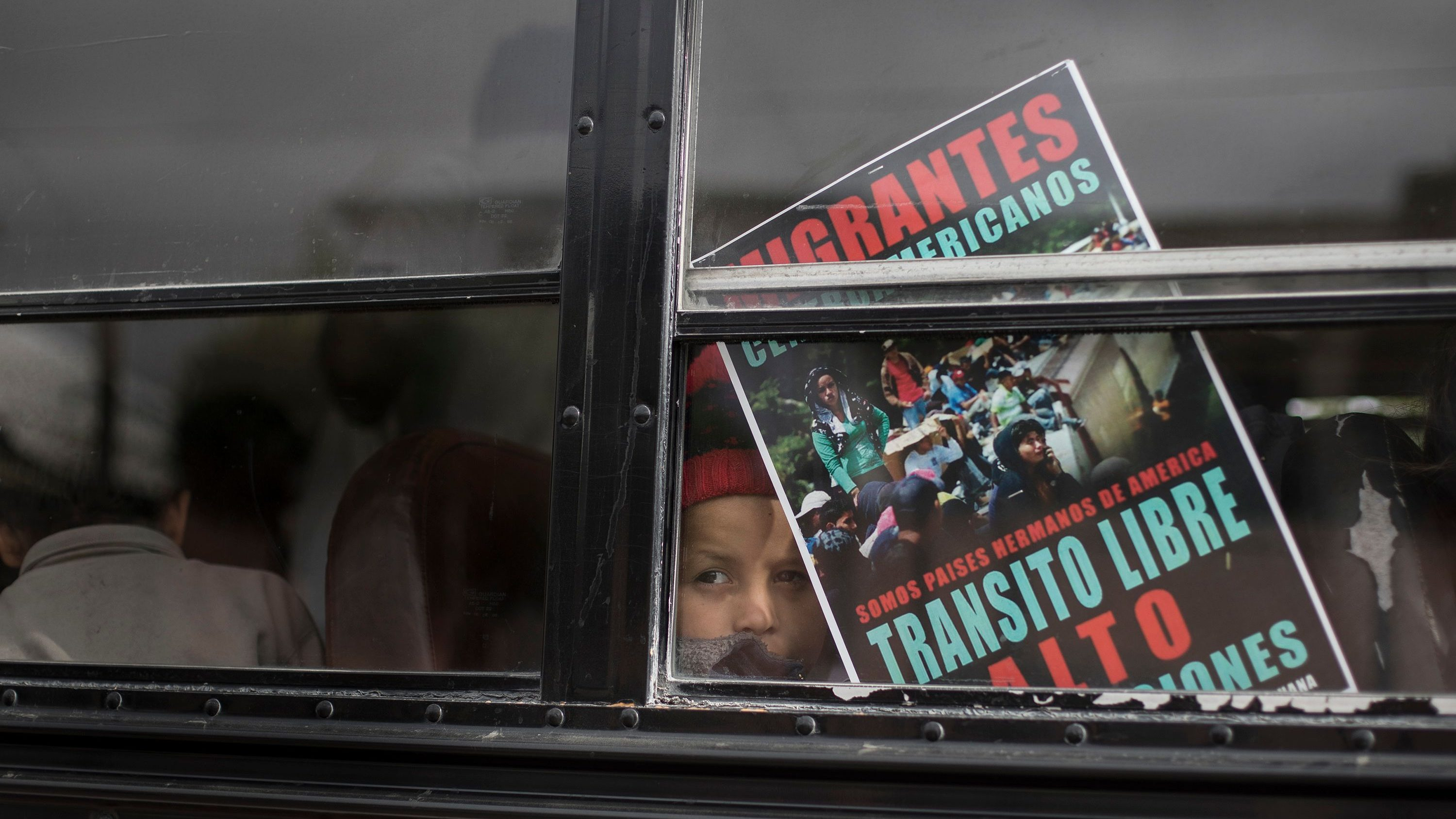 """A Central American child who is traveling with a caravan of migrants, peers from a bus carrying the group to the border wall for a gathering of migrants living on both sides of the border, in Tijuana, Mexico, Sunday, April 29, 2018. The sign reads in Spanish: We're all brother countries from the Americas. Free transit. Stop the deportations."""" (AP Photo/Hans-Maximo Musielik)"""