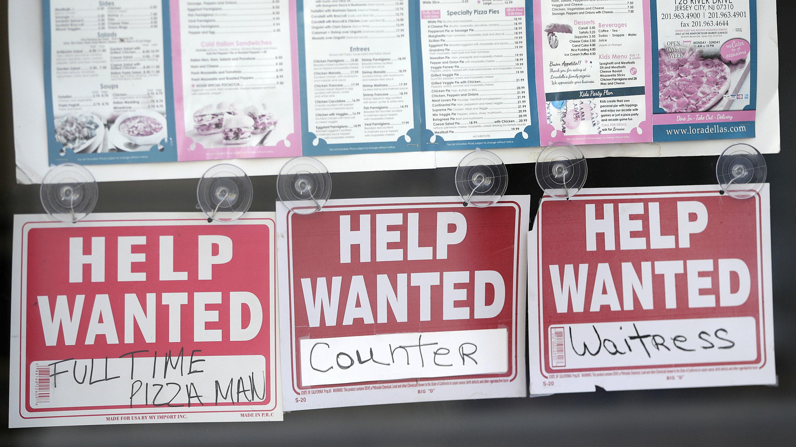 Help wanted signs hang below menus at a restaurant