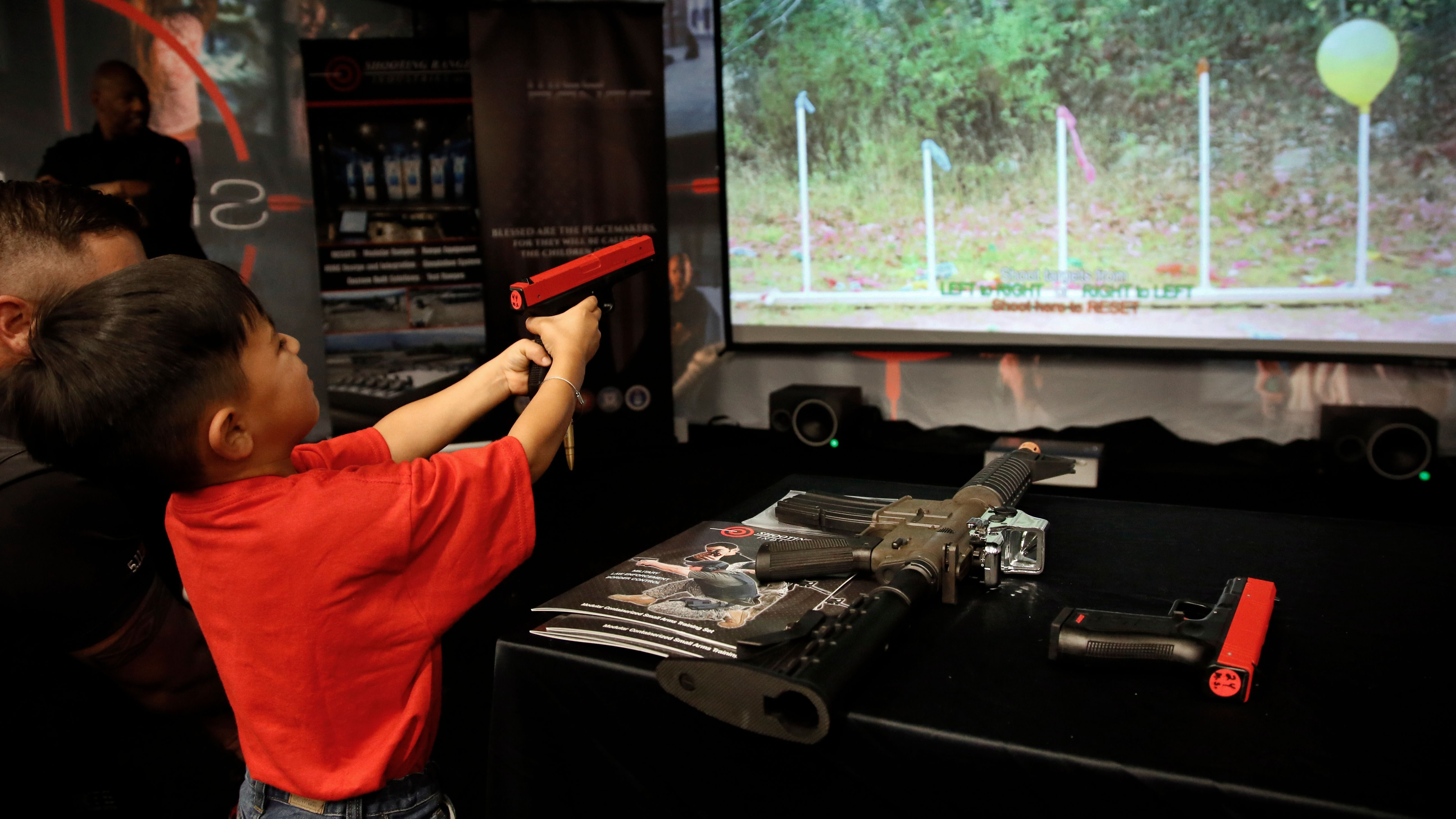 Ryland Hodge, 4, of Lakeland, Fla., aims at a balloons on a video display on an electronic gun range in the exhibit hall at the National Rifle Association convention in Dallas, Friday, May 4, 2018. (AP Photo/Sue Ogrocki)