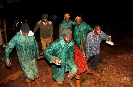 Members of the National Youth Service carry away a dead body covered in a blanket during the early hours of Thursday, May 10, 2018 near Solai, in Kenya's Rift Valley. Water burst through the banks of the Patel Dam in Nakuru County late Wednesday night after heavy rains, sweeping away hundreds of homes and killing dozens.