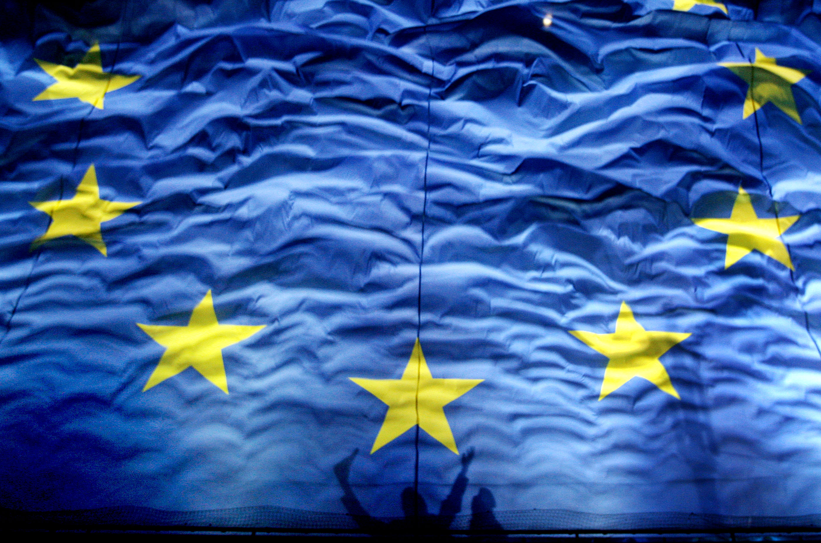 """FILE - In this Monday, Jan. 1, 2012 file photo, cheering Romanians cast shadows on a giant European Union  flag during new year celebrations for Romania's accesion in the EU in Bucharest Romania. The European Union has been awarded the Nobel Peace Prize for its efforts to promote peace and democracy in Europe, in the midst of the union's biggest crisis since its creation in the 1950s. The Norwegian prize committee said the EU received the award for six decades of contributions """"to the advancement of peace and reconciliation, democracy and human rights in Europe. (AP Photo/Vadim Ghirda, File)"""