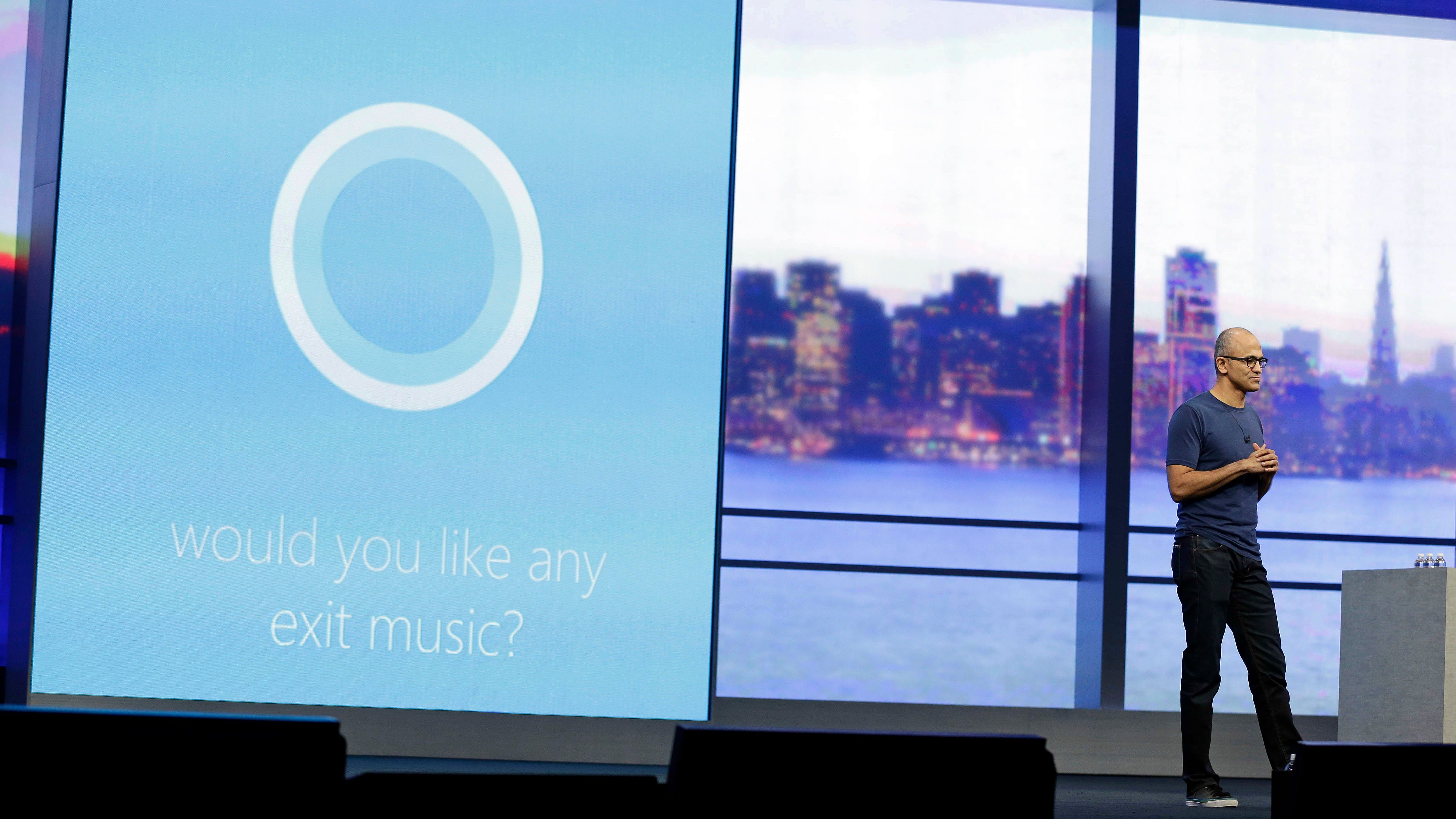 Microsoft CEO Satya Nadella carries on a conversation with the new personal assistant Cortana at the end of his keynote address to the Build Conference Wednesday, April 2, 2014, in San Francisco. Microsoft kicked off its annual conference for software developers, with new updates to the Windows 8 operating system and upcoming features for Windows Phone and Xbox. (AP Photo/Eric Risberg)