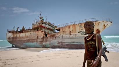 In this photo taken Sunday, Sept. 23, 2012, masked Somali pirate Abdi Ali stands near a Taiwanese fishing vessel that washed up on shore after the pirates were paid a ransom and released the crew, in the once-bustling pirate den of Hobyo, Somalia. The empty whisky bottles and overturned, sand-filled skiffs that litter this shoreline are signs that the heyday of Somali piracy may be over - most of the prostitutes are gone, the luxury cars repossessed, and pirates talk more about catching lobsters than seizing cargo ships.
