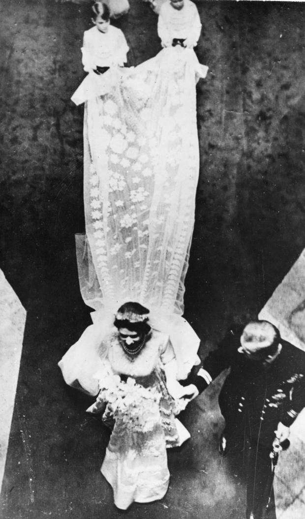 Seen from above are the Royal newly-weds, British Princess Elizabeth and Lieutenant Philip Mountbatten (Duke of Edinburgh) as they leave Westminster Abbey, London, November 20, 1947. After their marriage, shows the bridal train. The 15-foot long bridal train is of transparent ivory silk, attached to the shoulders and edged with graduated satin flowers, finally forming a deep border encrusted with pearls and crystals. (AP Photo)